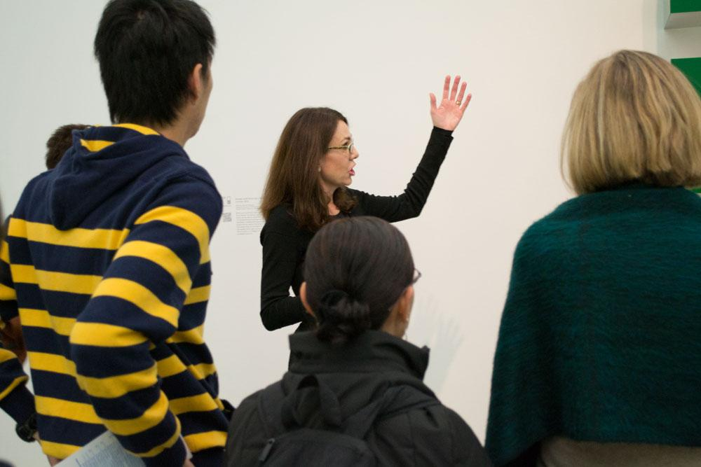 A female tour guide gestures to her left in front of several onlookers.