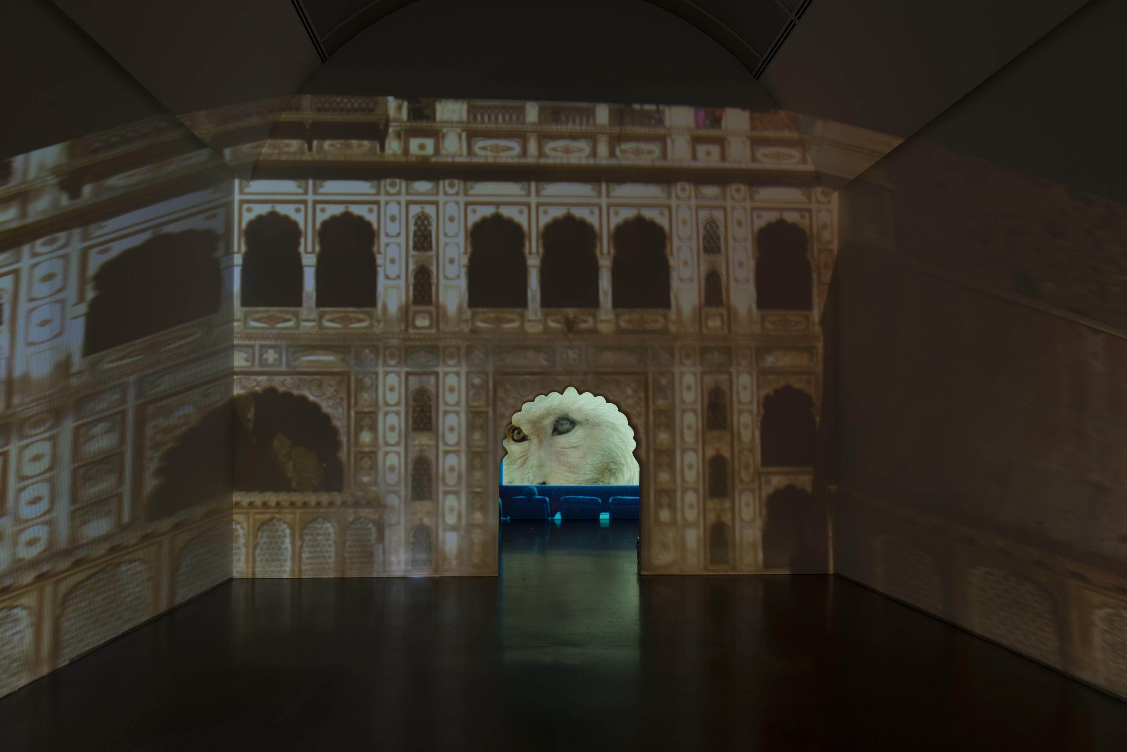The facade of a temple in ruins is projected onto three walls. A scalloped doorway in the middle reveals a close-up projection of a monkey's face in the room beyond.