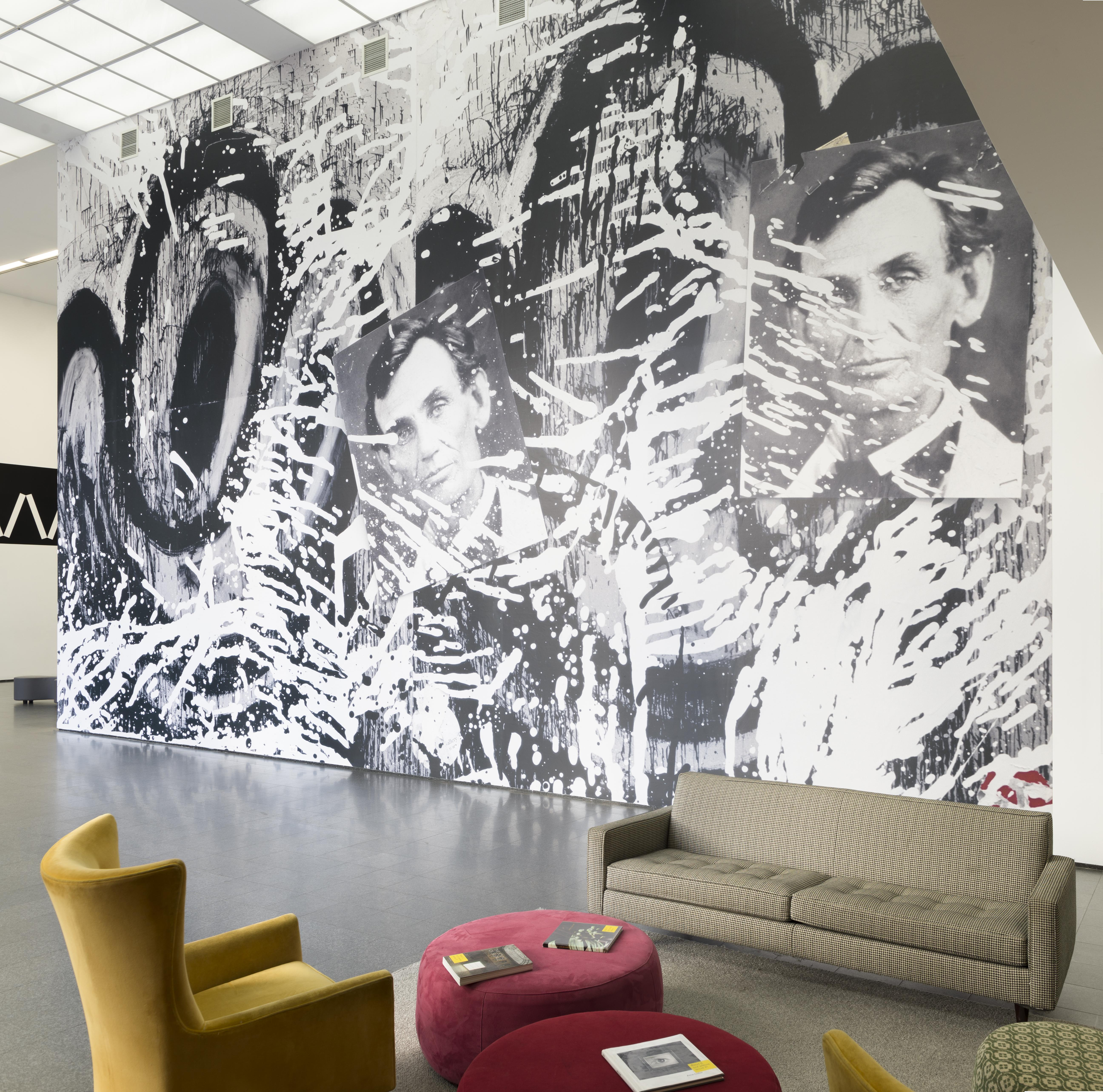 An image of a huge photographic wallpaper mural in the MCA's second floor lobby featuring cartoonish eyes, two photographs of Abraham Lincoln, and splatters of black and white paint. A setting of living room furniture is in the foreground of the image.