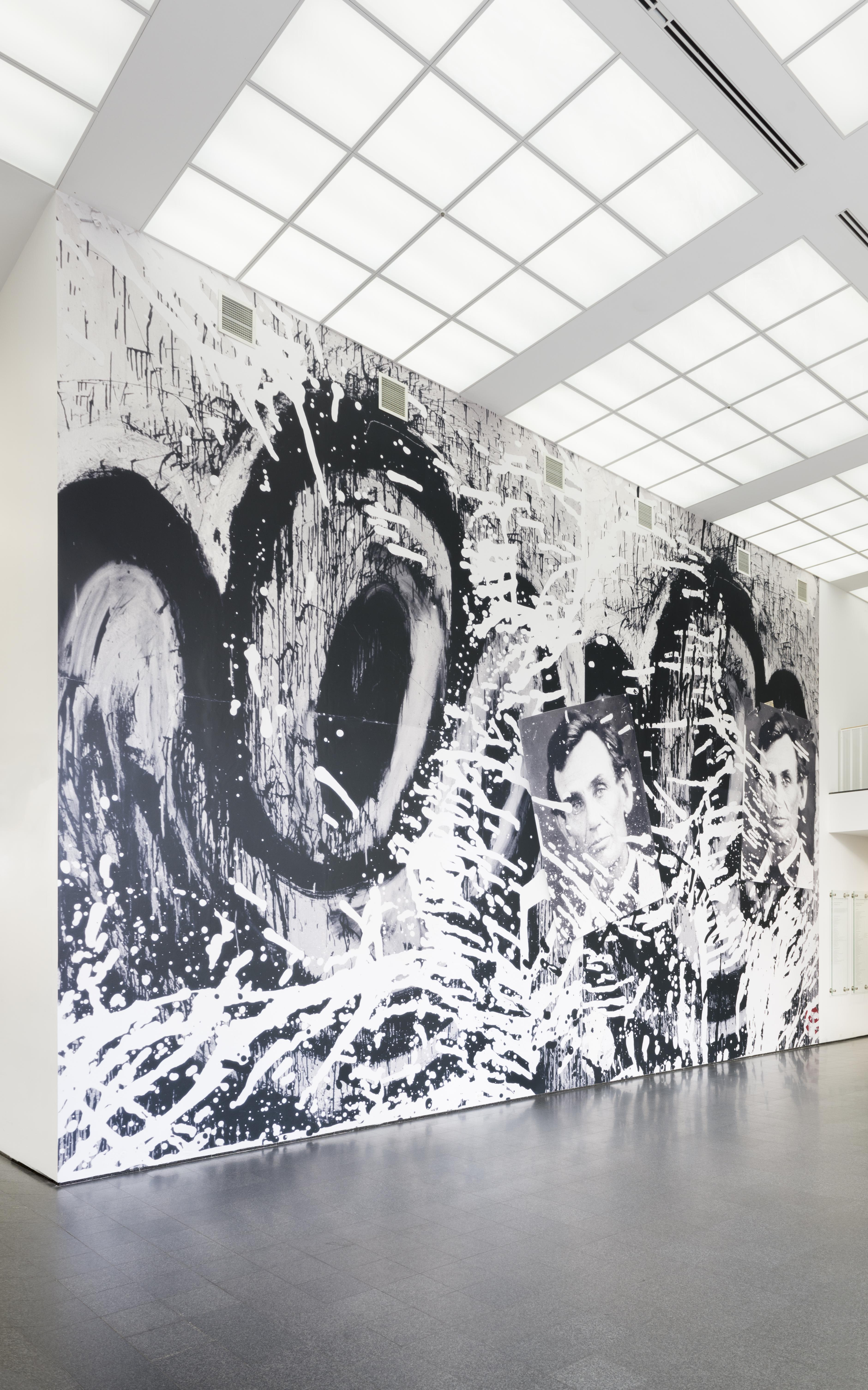 An image of a huge photographic wallpaper mural in the MCA's second floor lobby featuring cartoonish eyes, two photographs of Abraham Lincoln, and splatters of black and white paint.