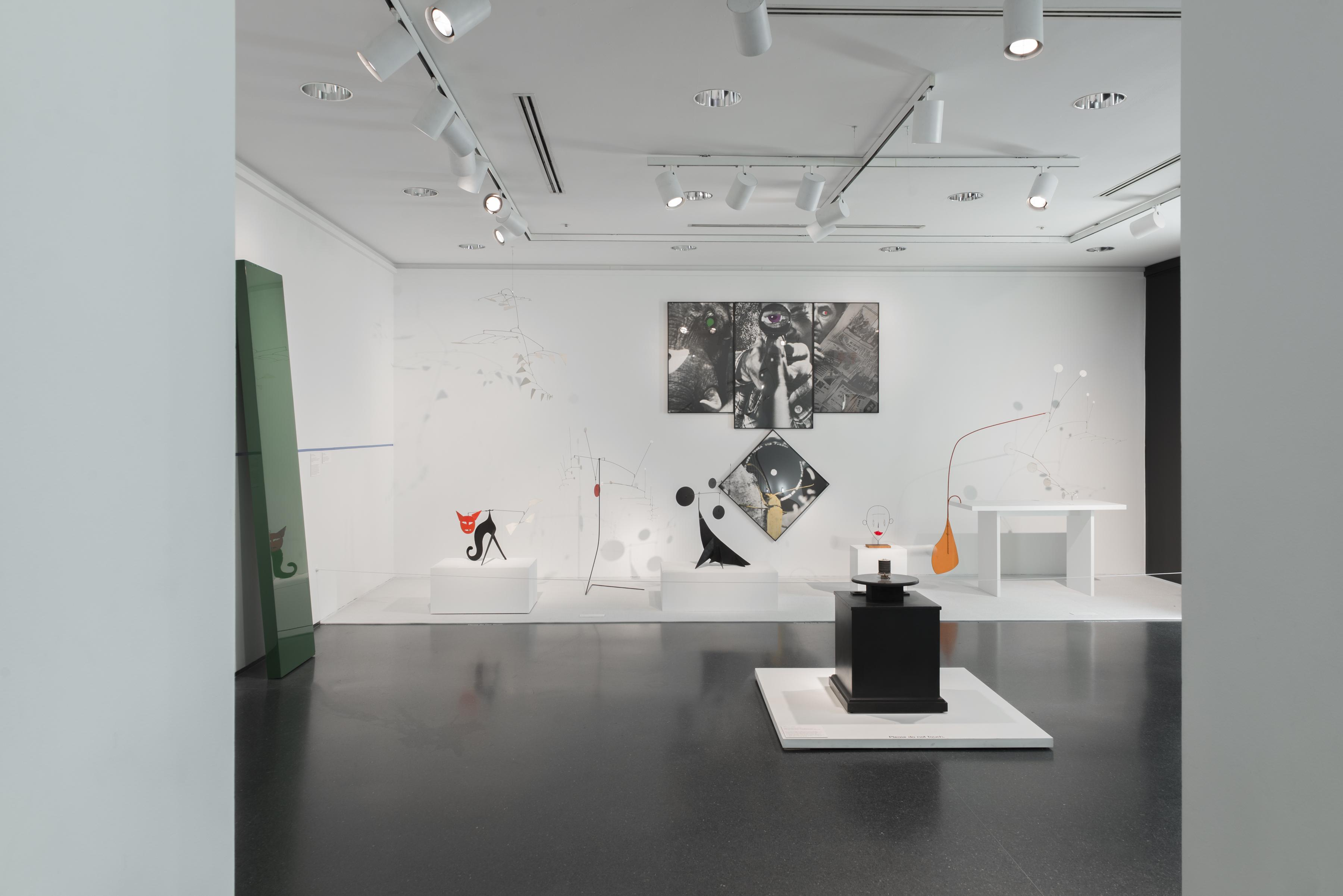 Several mobile sculptures in various shapes rest on pedestals or hang from the ceiling in front of a large multipaneled black-and-white photograph in a white-walled gallery.