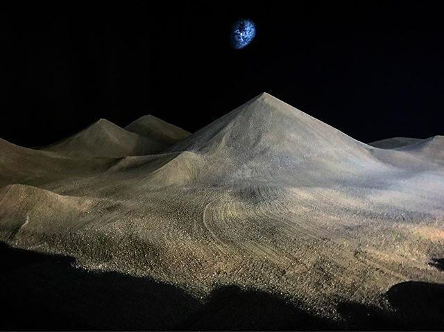 In a dark room, a large mound of sand forms several cone shapes, while a small light projection in the background shows an abstract, vaporous shape that resembles a planet.