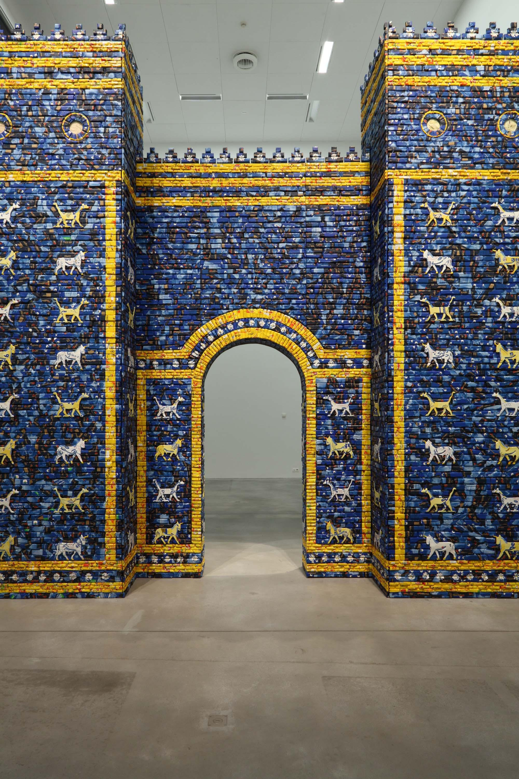 An architectural arched gateway is shown, installed within a modern gallery space. The arch is made from bricks in a range of different blues with golden yellow accents and decorated with stylized animals.