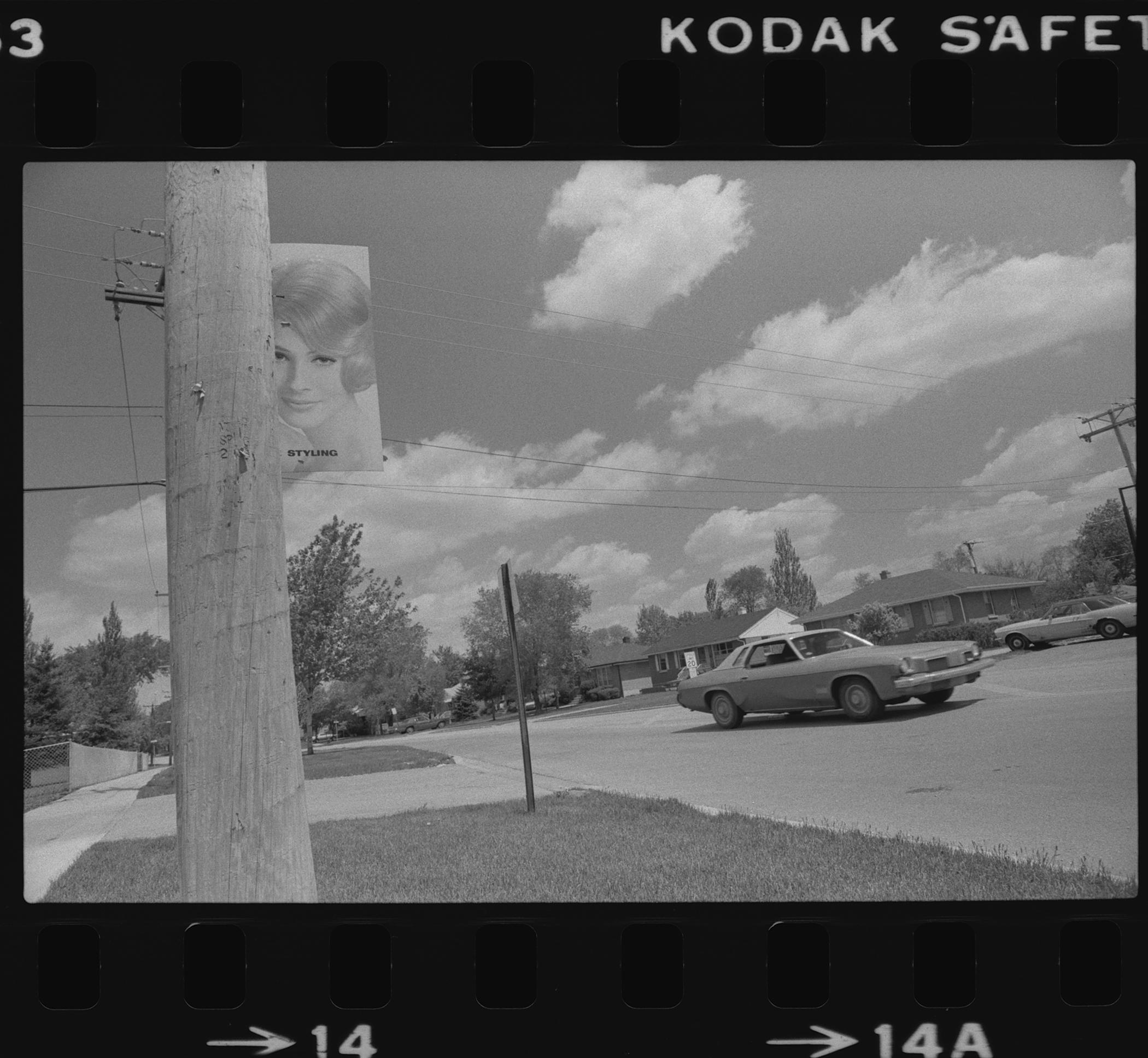 """A black-and-white film frame shows a car driving along a suburban street. In the foreground is a wooden utility pole affixed with a poster of a woman and the the word """"STYLING""""."""