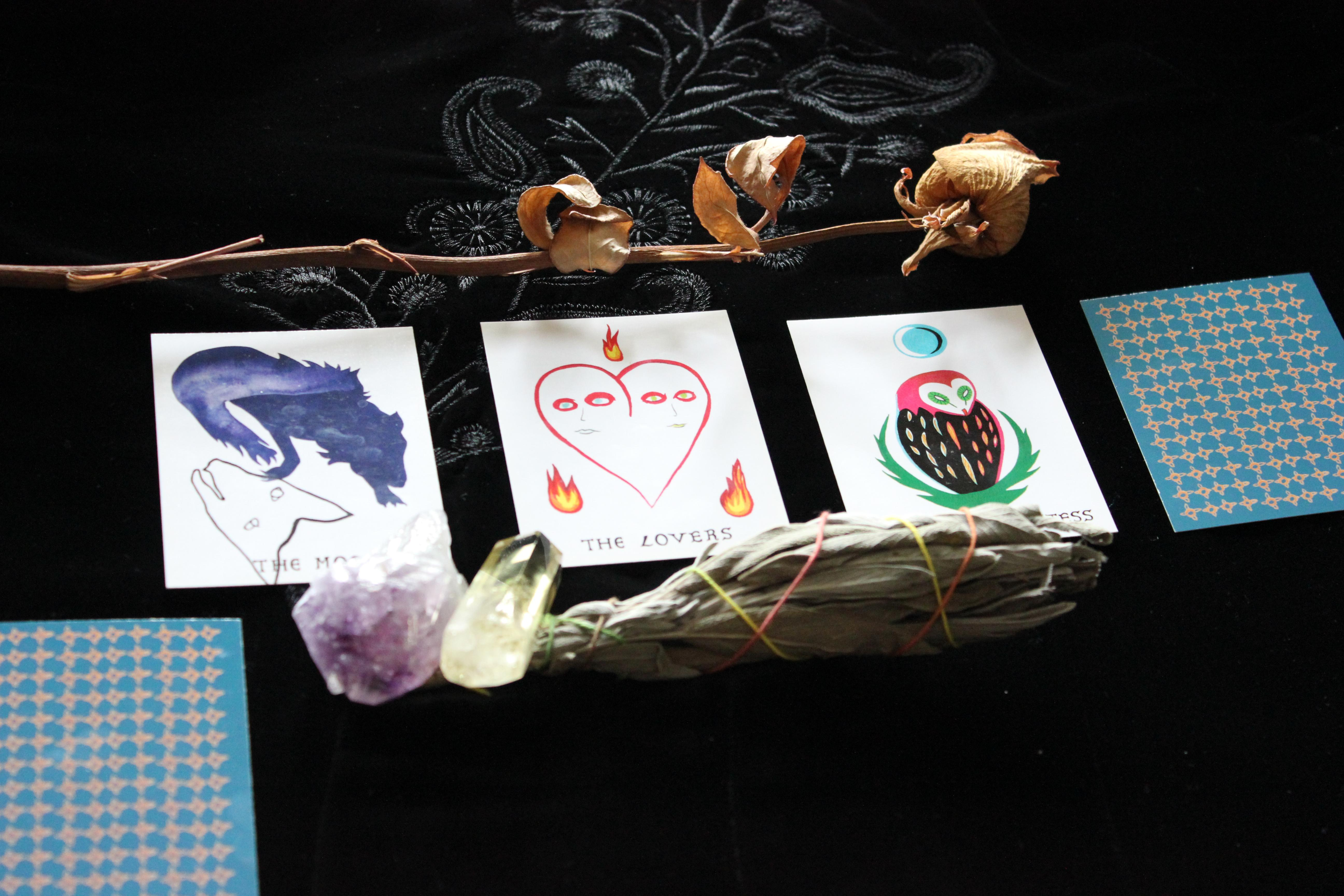 Four tarot cards are placed in a row on an embroidered black tablecloth. Three of the four cards reveal an image. A dried rose frames the top of the photo. Two crystals and a smudging stick are in the foreground. A fifth unrevealed card is cut off in the lower left corner.