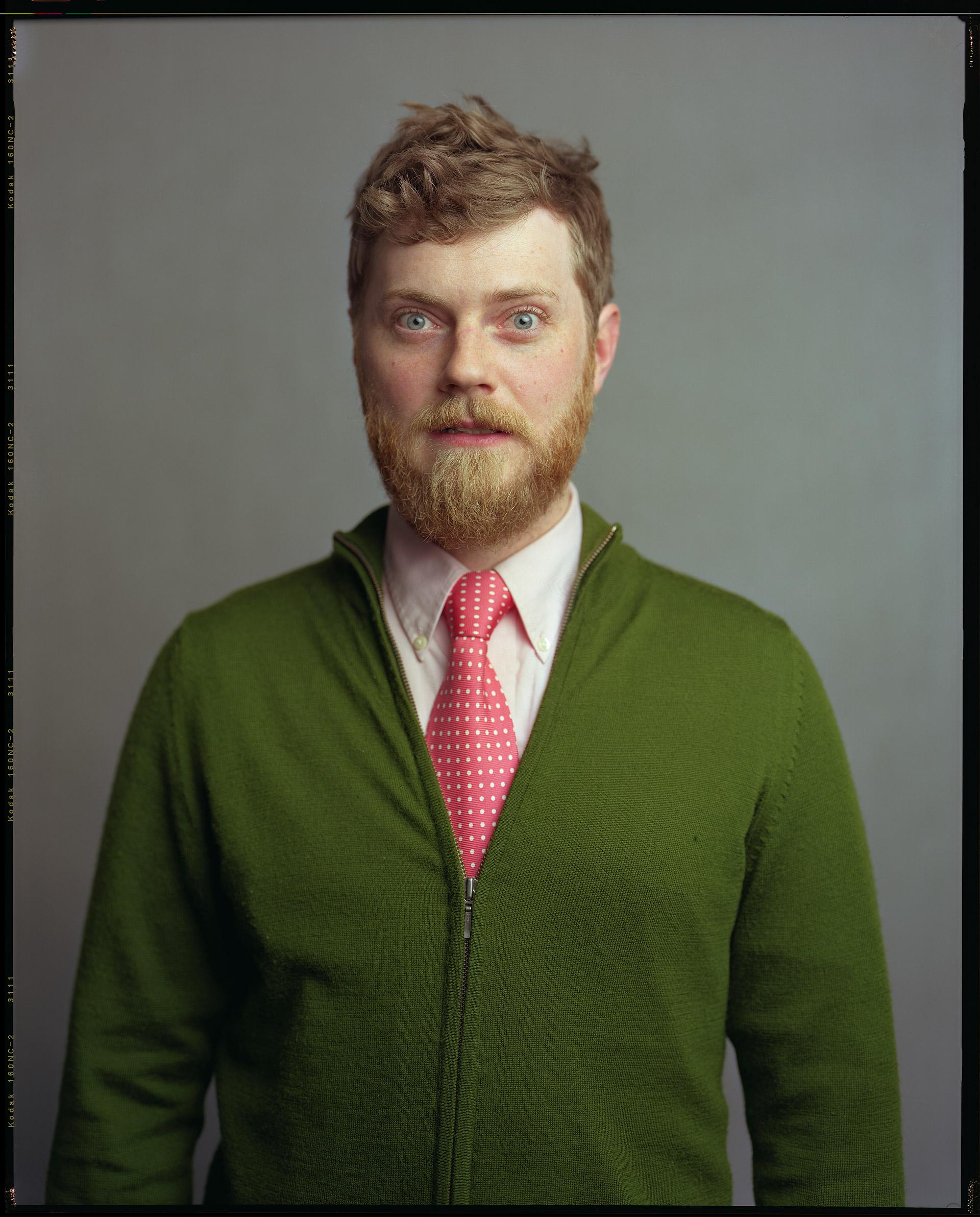 A pale-skinned person with red hair and a red beard and mustache is wearing a green zip-up sweater and pink tie.