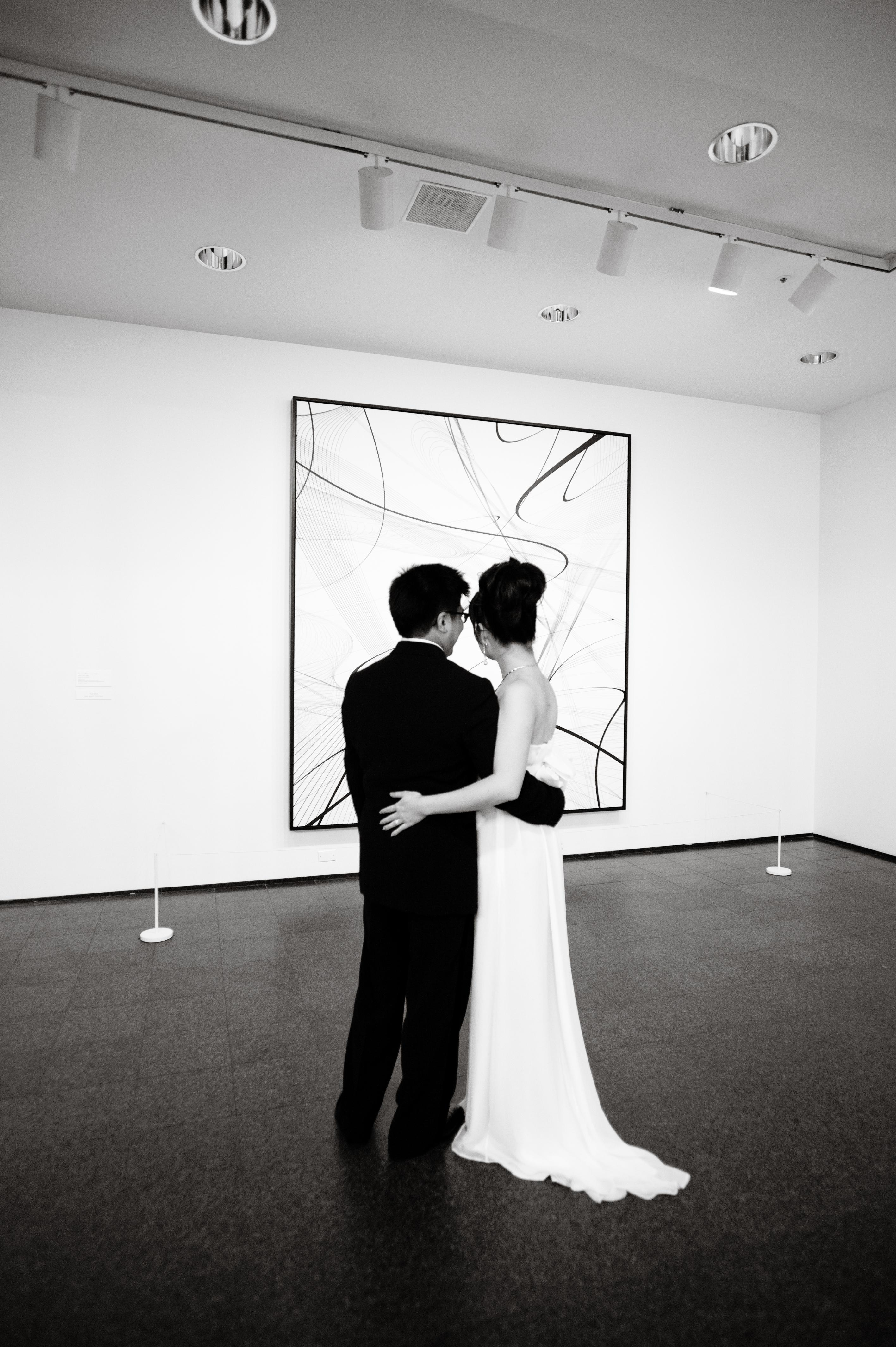 A bride and groom embrace in front of an artwork, with their backs to the camera.