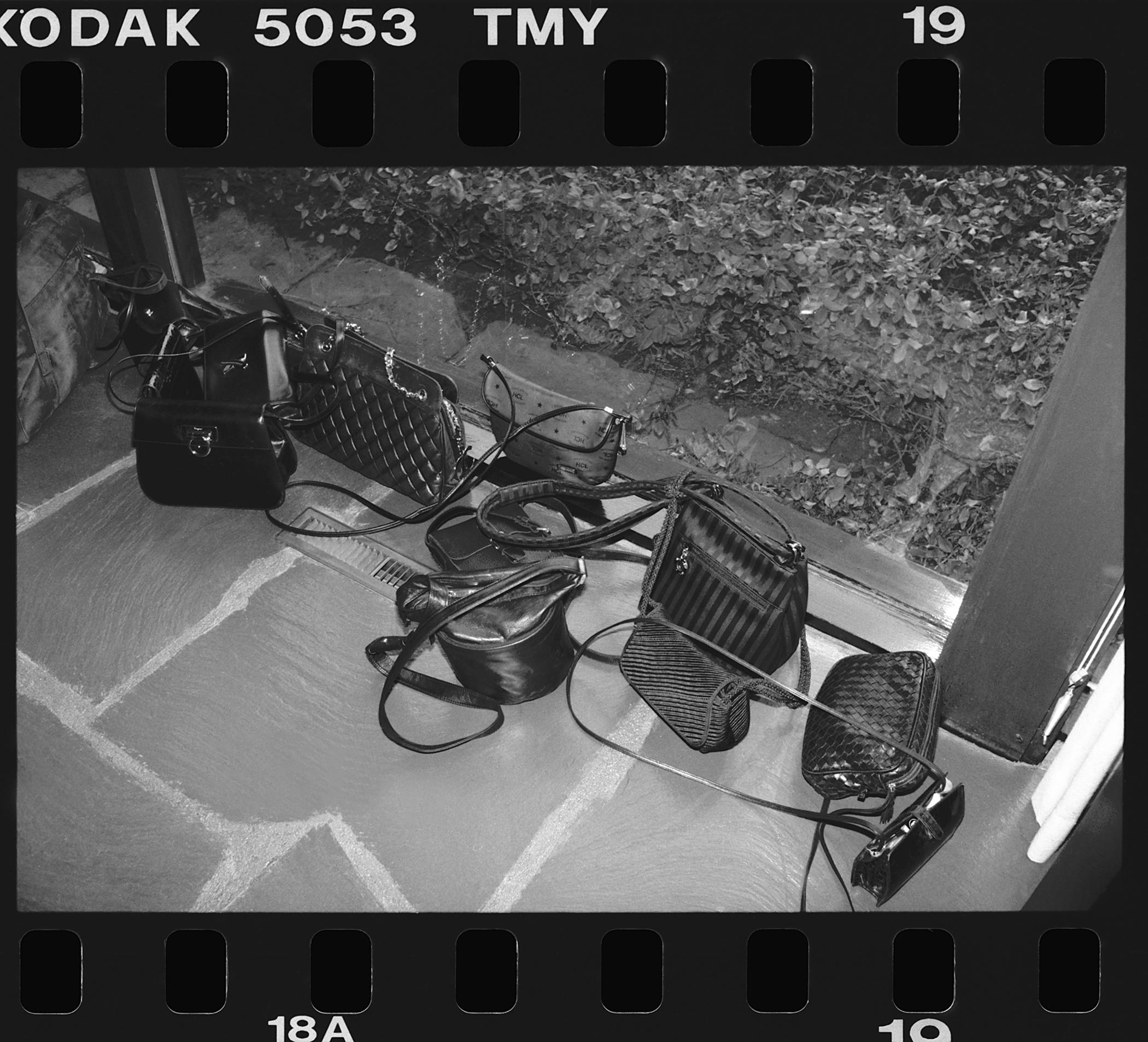 This black-and-white 35 mm film frame depicts nine purses of varying shapes and sizes on a stone floor next to a glass window.