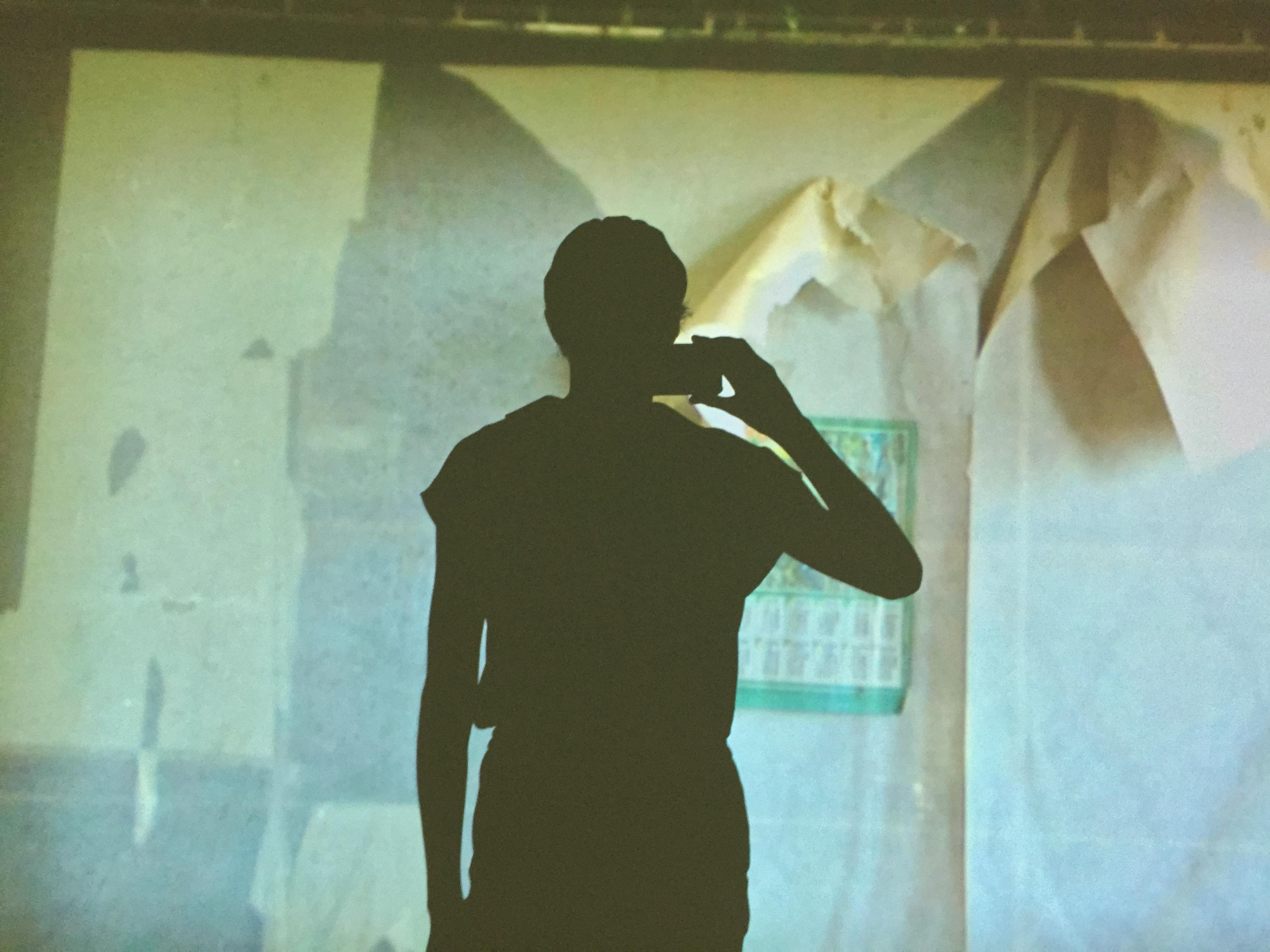 A silhouette of a person photographing a video projection on a wall. The video projection appears to be a room of peeling wallpaper.