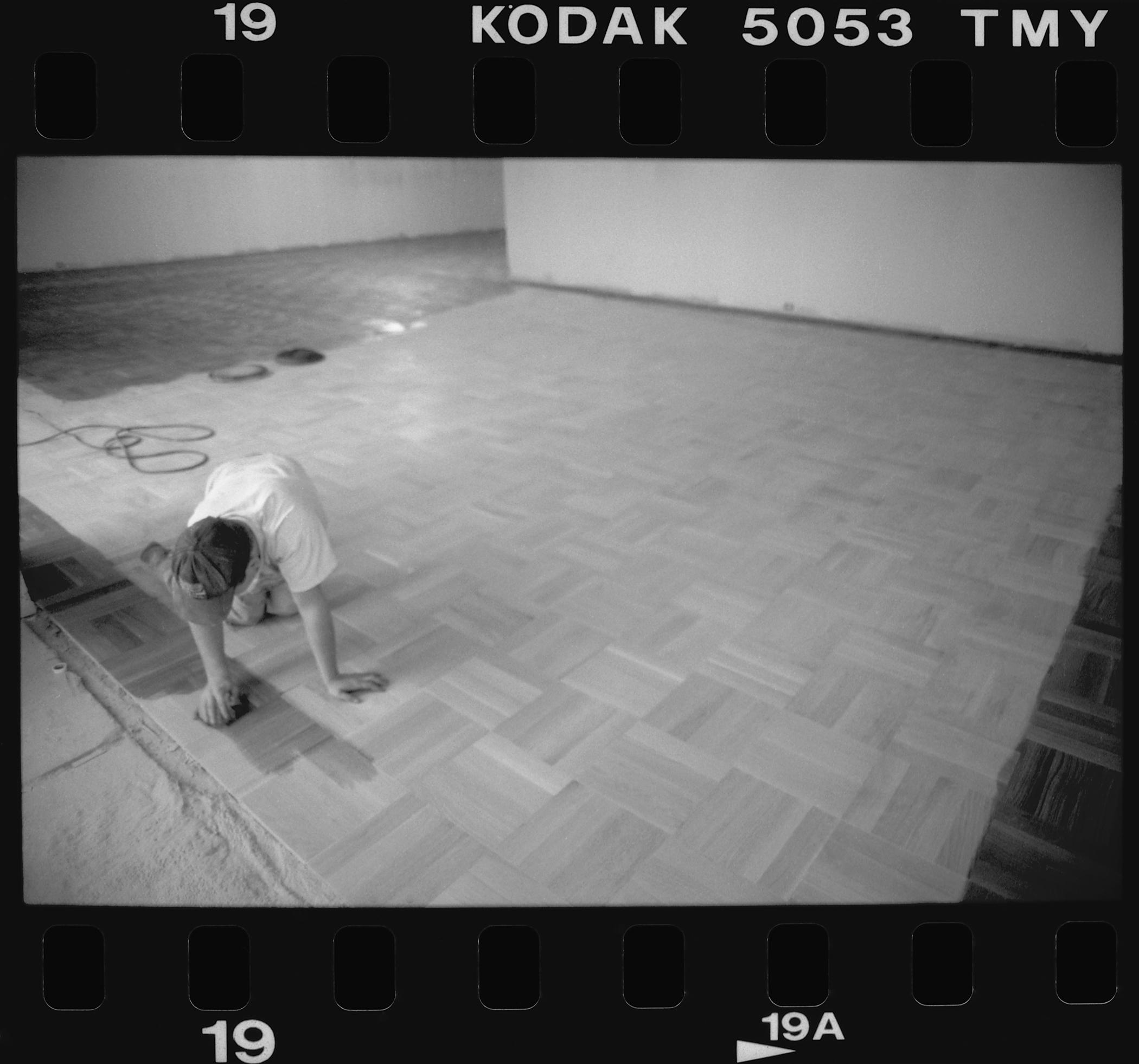 A person on hands and knees installs wooden parquet flooring.