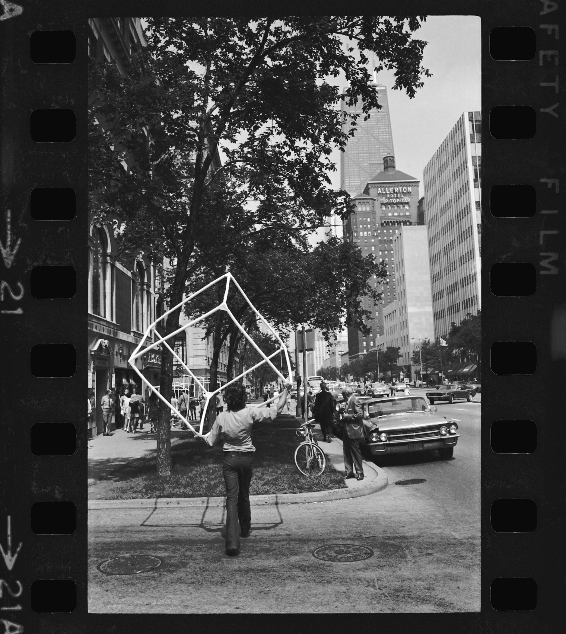 A black-and-white film frame shows a woman carrying an open cube sculpture while crossing the street, heading North on Michigan Avenue, Chicago, with the Allerton and John Hancock buildings in the background.