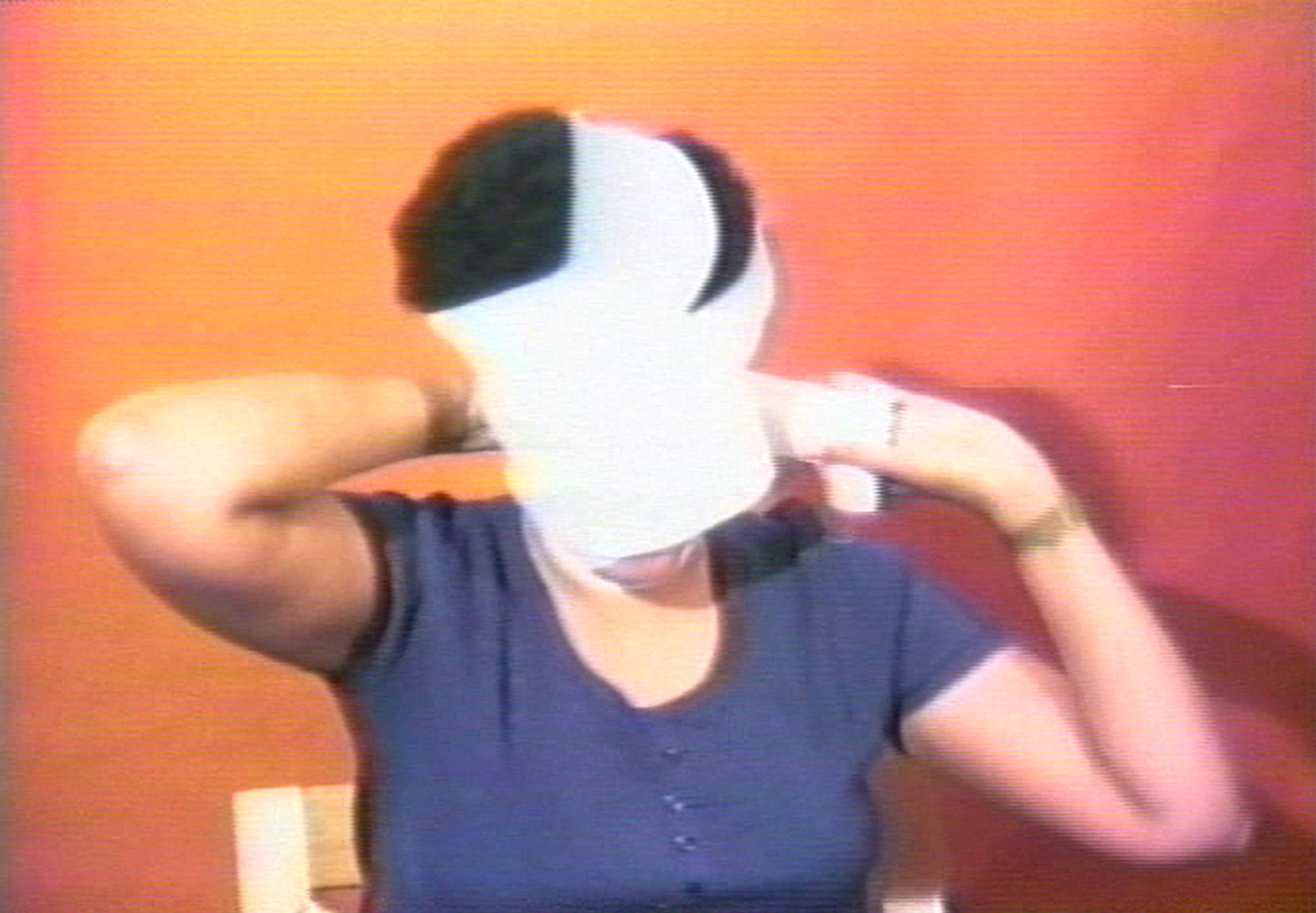 In this grainy image, a woman with a black afro is shown wrapping her face with a white bandage.