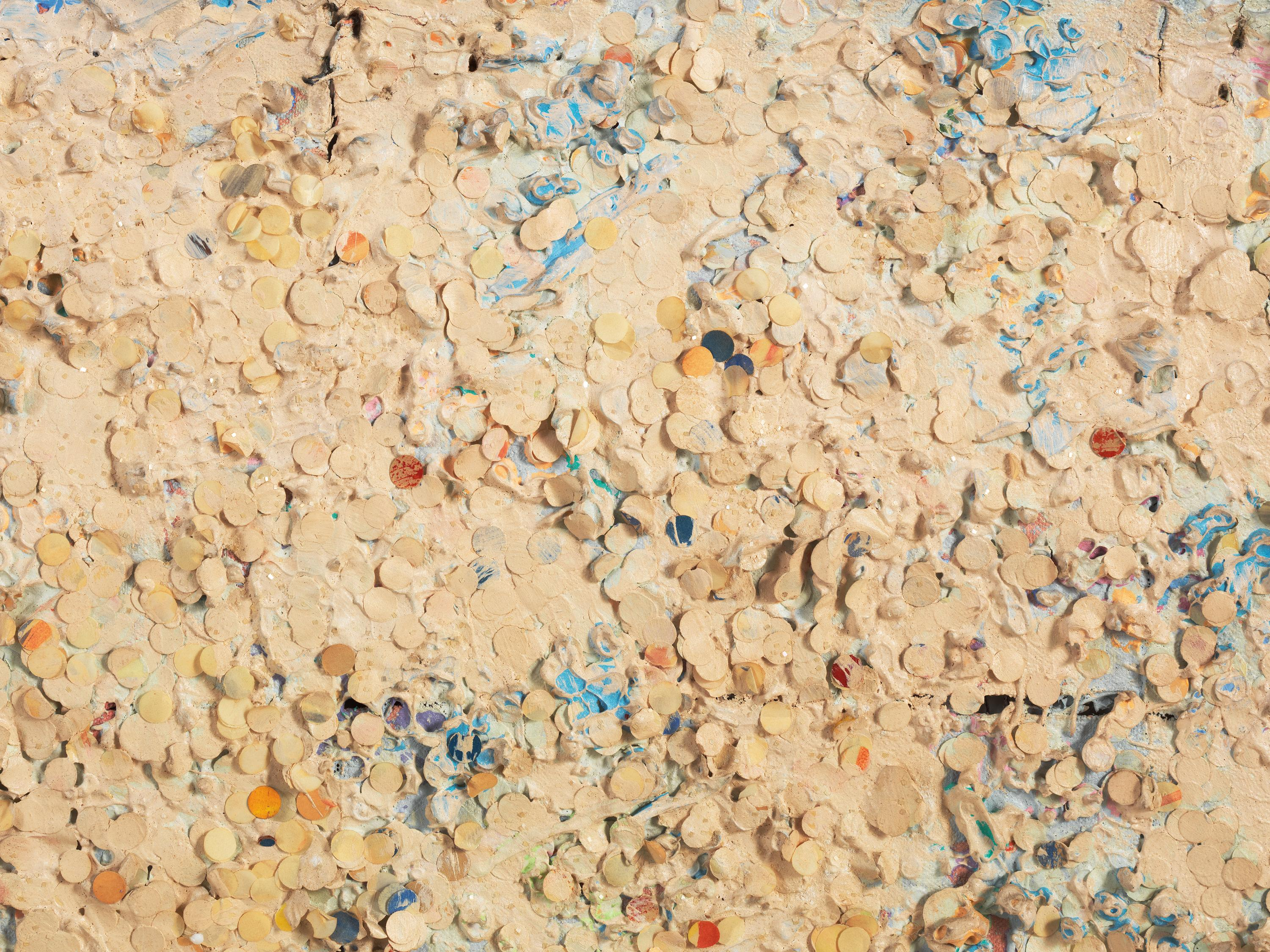 A beige, textured surface covered in small circles is accented with hints of blue, orange, and red paint.