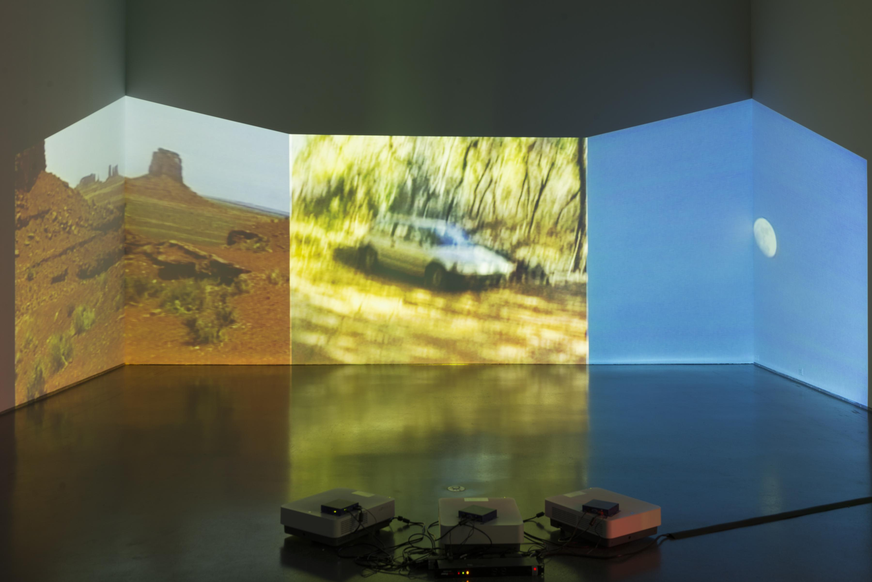 Three projectors on the floor project three different images on the opposite wall: a southwestern desert landscape, a car in golden light, and a small moon on a blue sky. The images are projected on the corners of the room, creating irregular viewing frames.