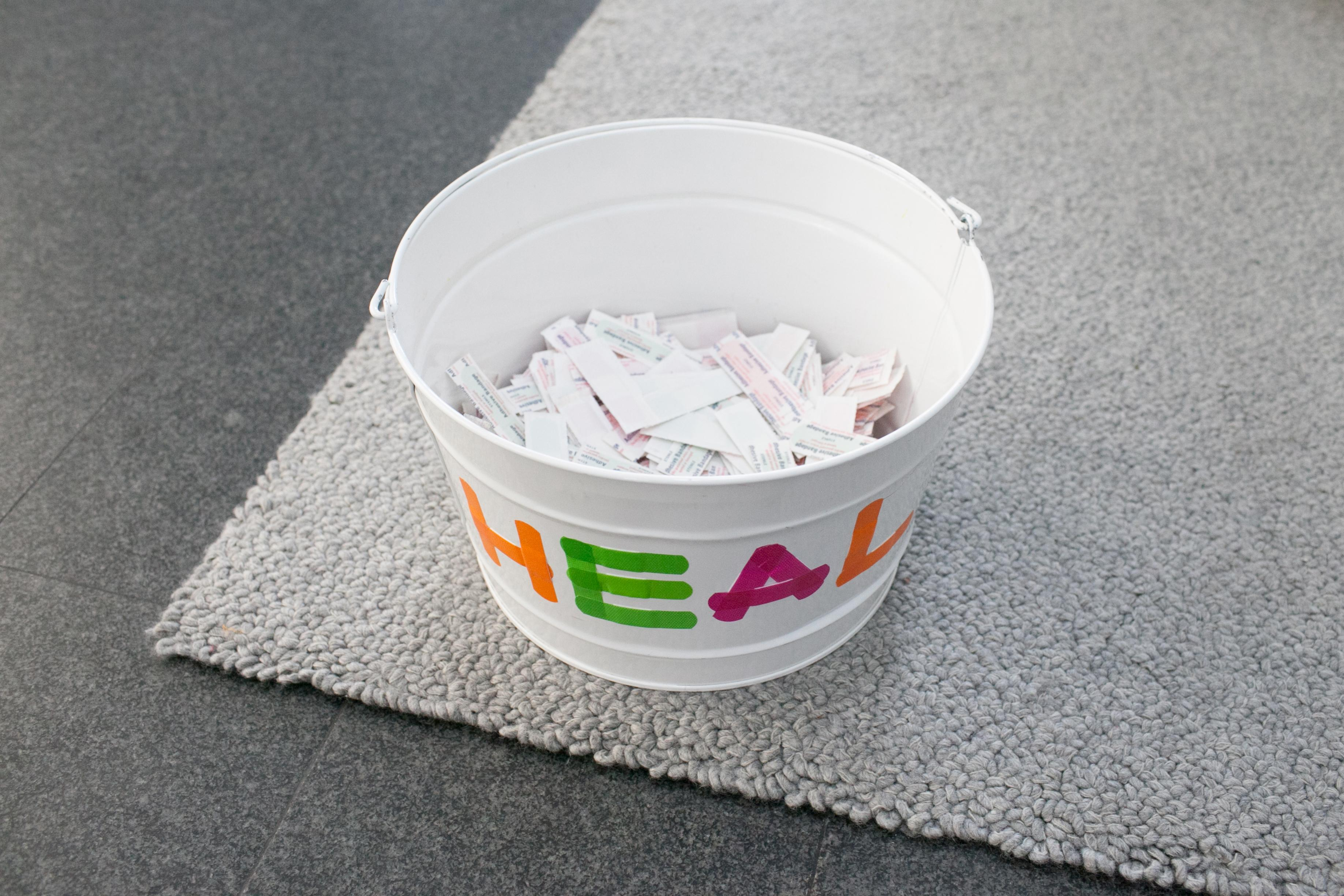 """A white pail labeled """"HEAL"""" in bright colors sits on the corner of a gray rug, which in turn rests on a gray granite floor. The pail is half-way filled with slips of paper."""