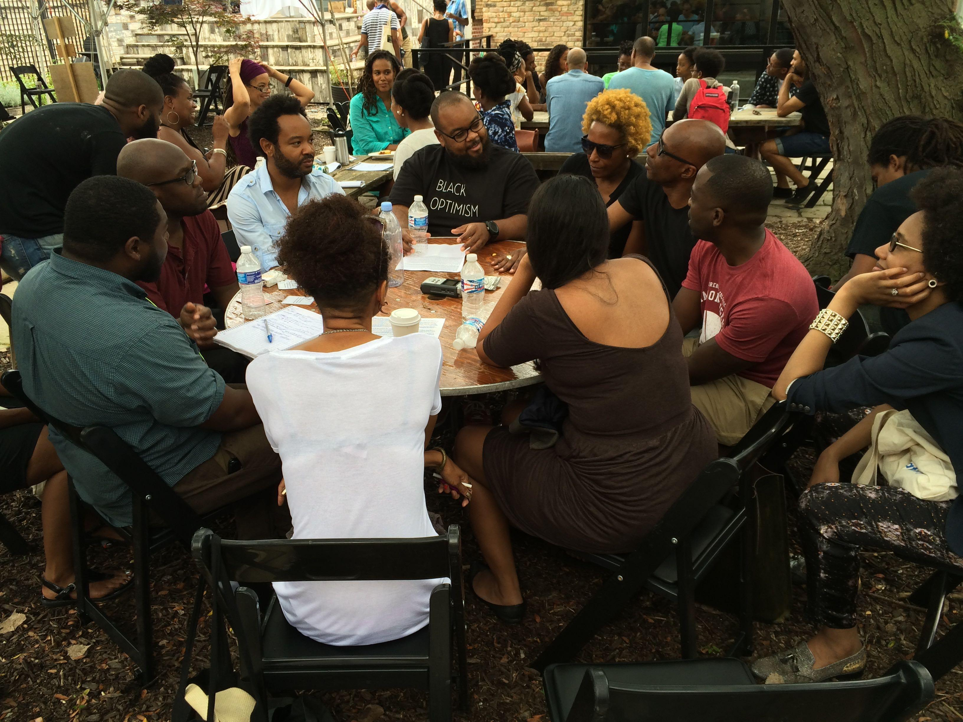 A group of dark-skinned people sit talking around a table outdoors, with other tables of people visible in the background.