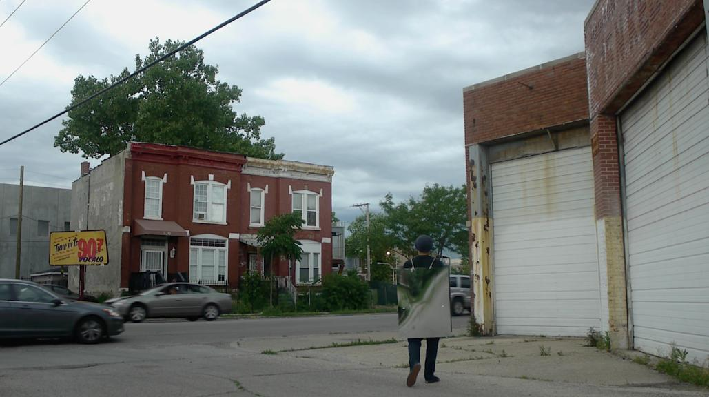 On a cloudy day, a man with his back to the camera, wearing a walking sandwich board sign made of reflective material stands in an urban outdoor environment surrounded by an old garage, some cars, trees and brick buildings.