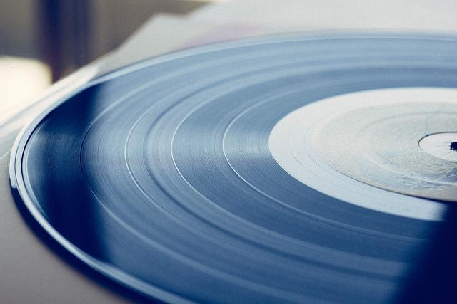 A vinyl record disc is cropped in half, its center is aligned with the right side of the image.