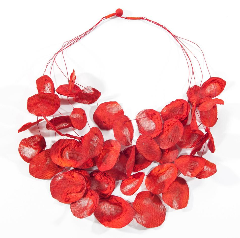 A necklace with dozens of fire red rose petals that are hand fashioned from mesh and paper and threaded through multiple strands.