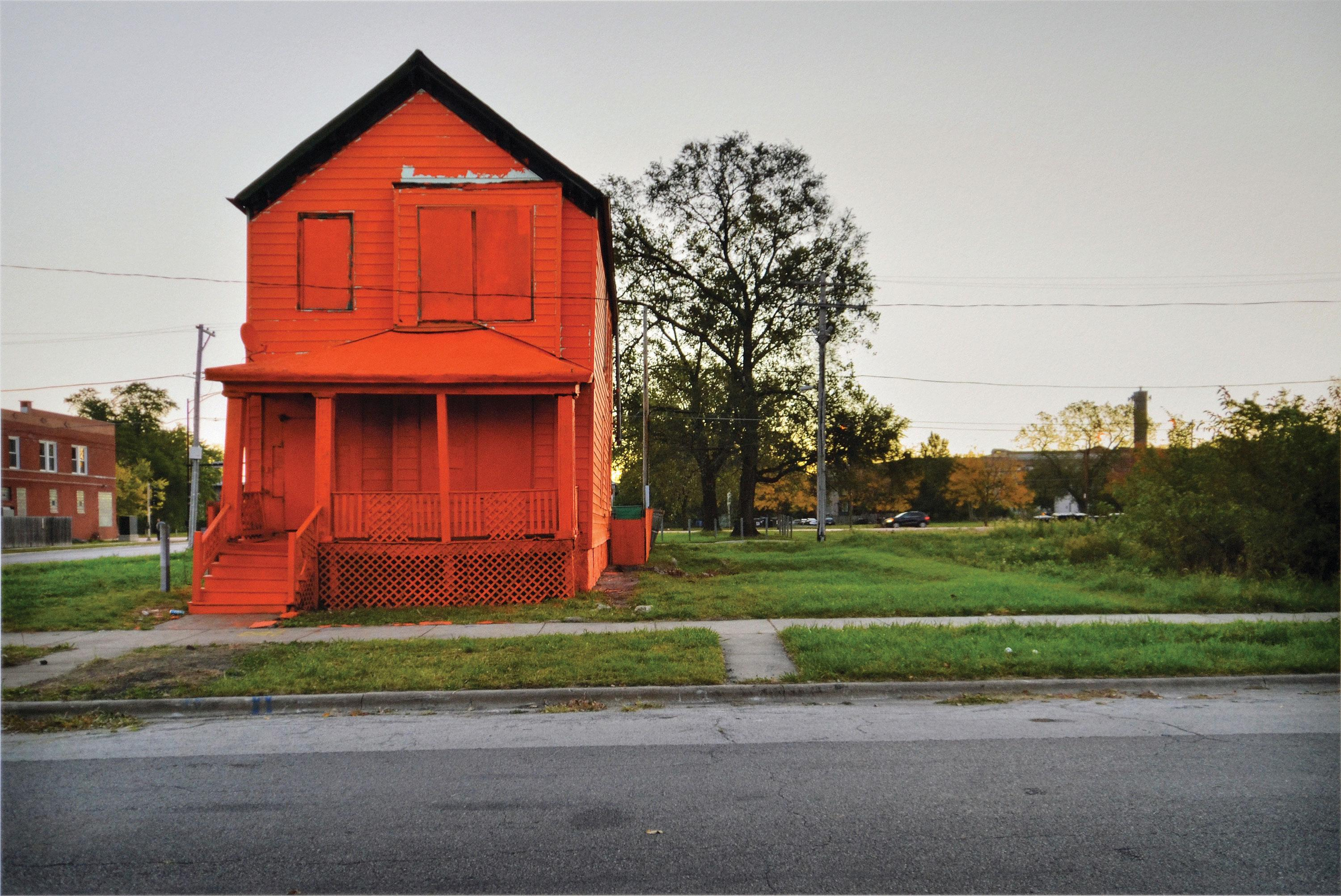 A bright red-orange house is boarded up, standing next to an empty urban lot during sunset.
