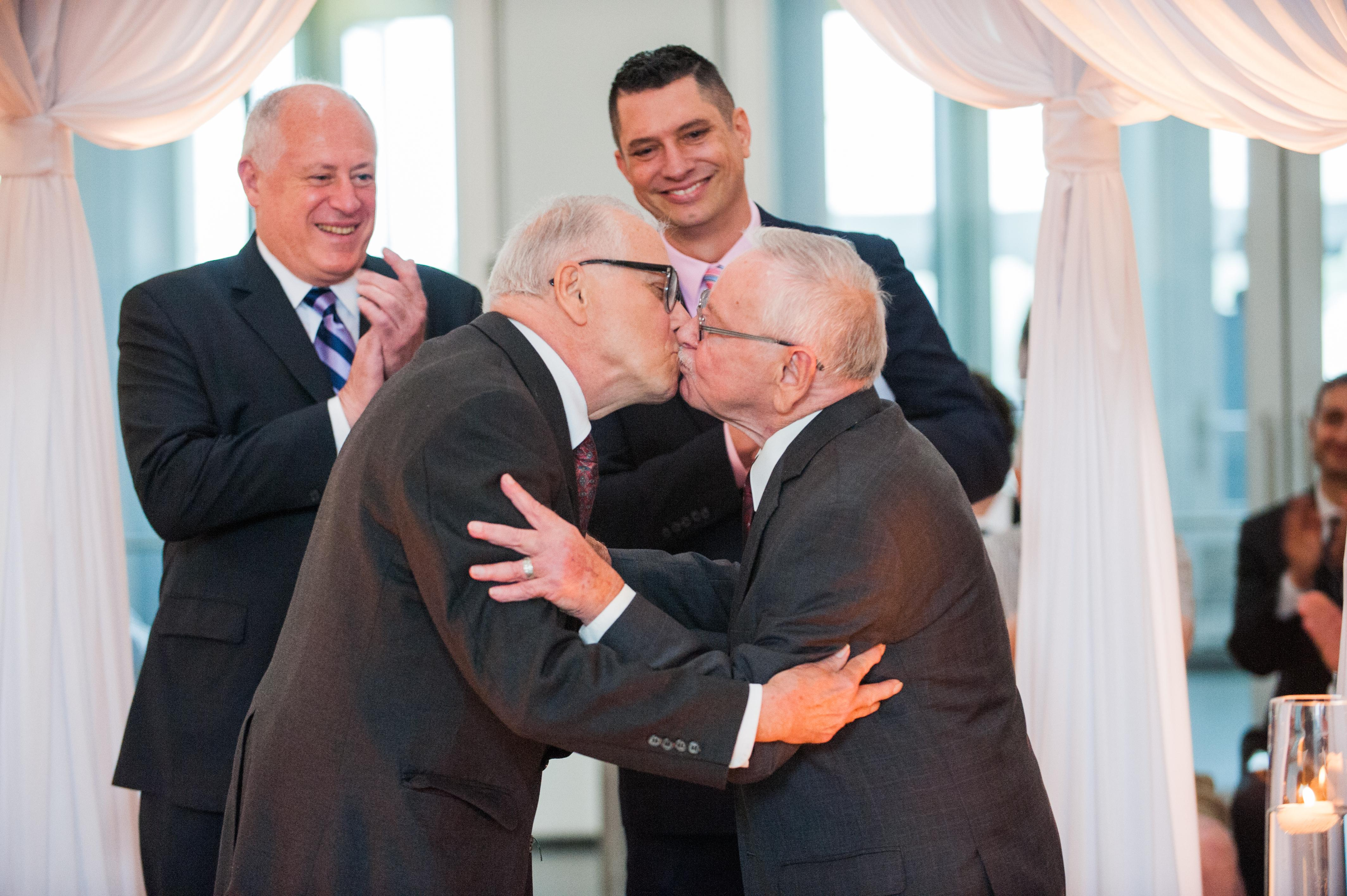 Two elderly men wearing suits embrace in a kiss while two other men look on smiling and clapping.