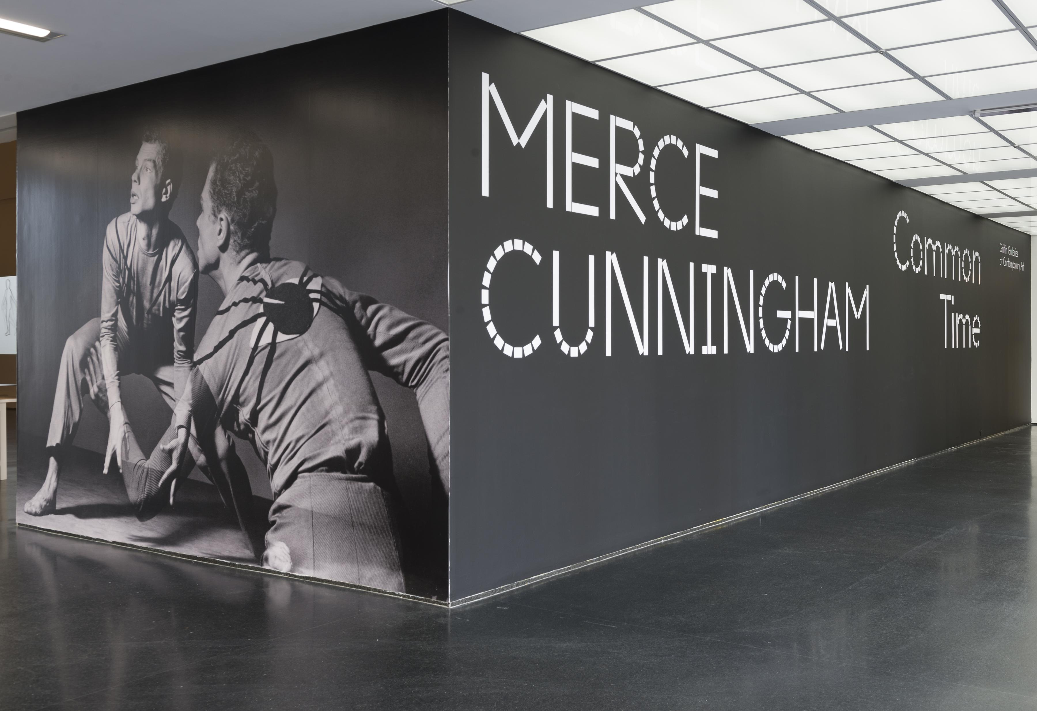 """A black-walled corner in a room features a floor-to-ceiling gray-scale image of a crouching man seen from the front and the back on the left wall, and large white letters on the adjacent black wall that read: """"MERCE CUNNINGHAM Common Time."""""""
