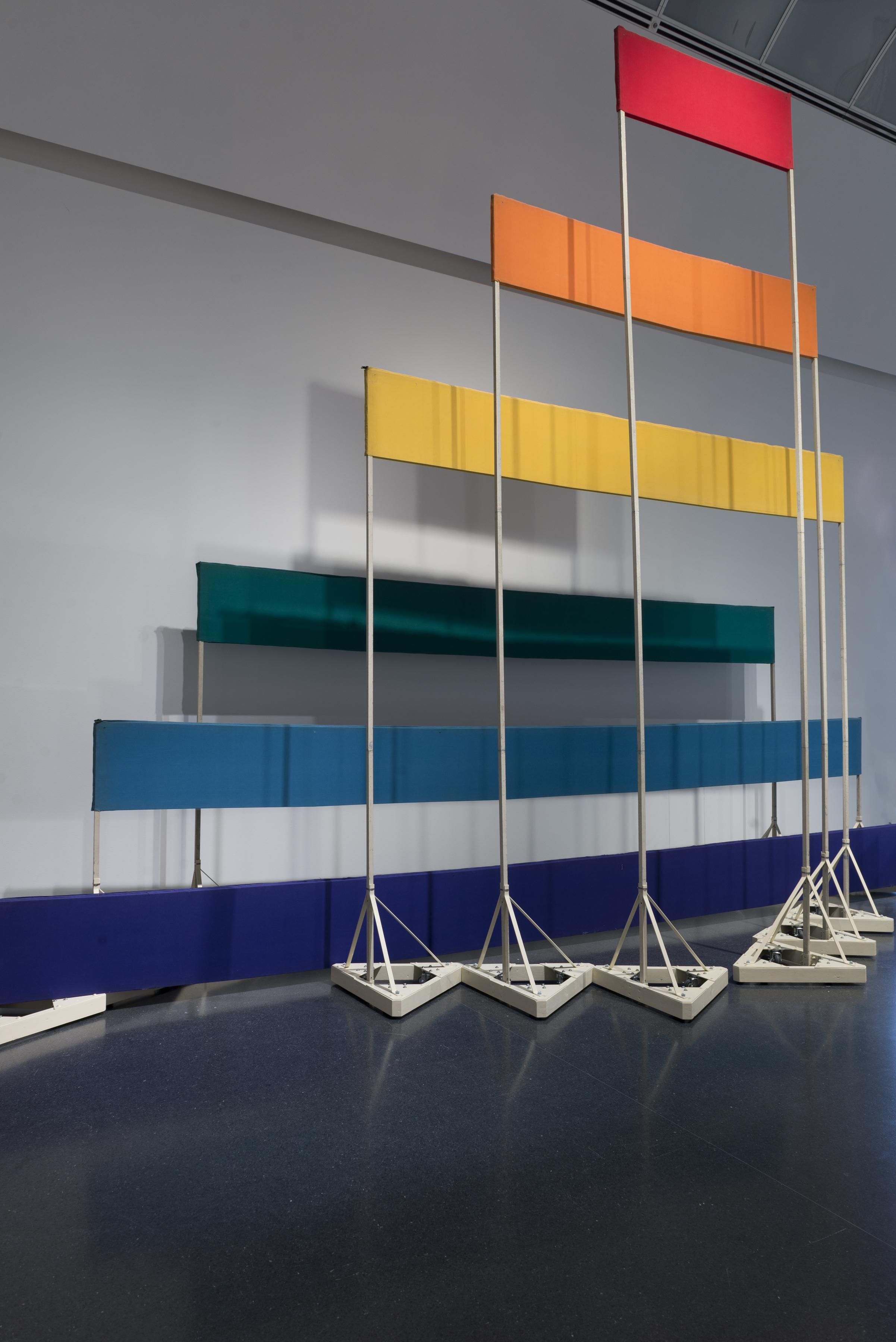 Six boards, each a different color and length, are supported by stands of increasing height and decreasing width.