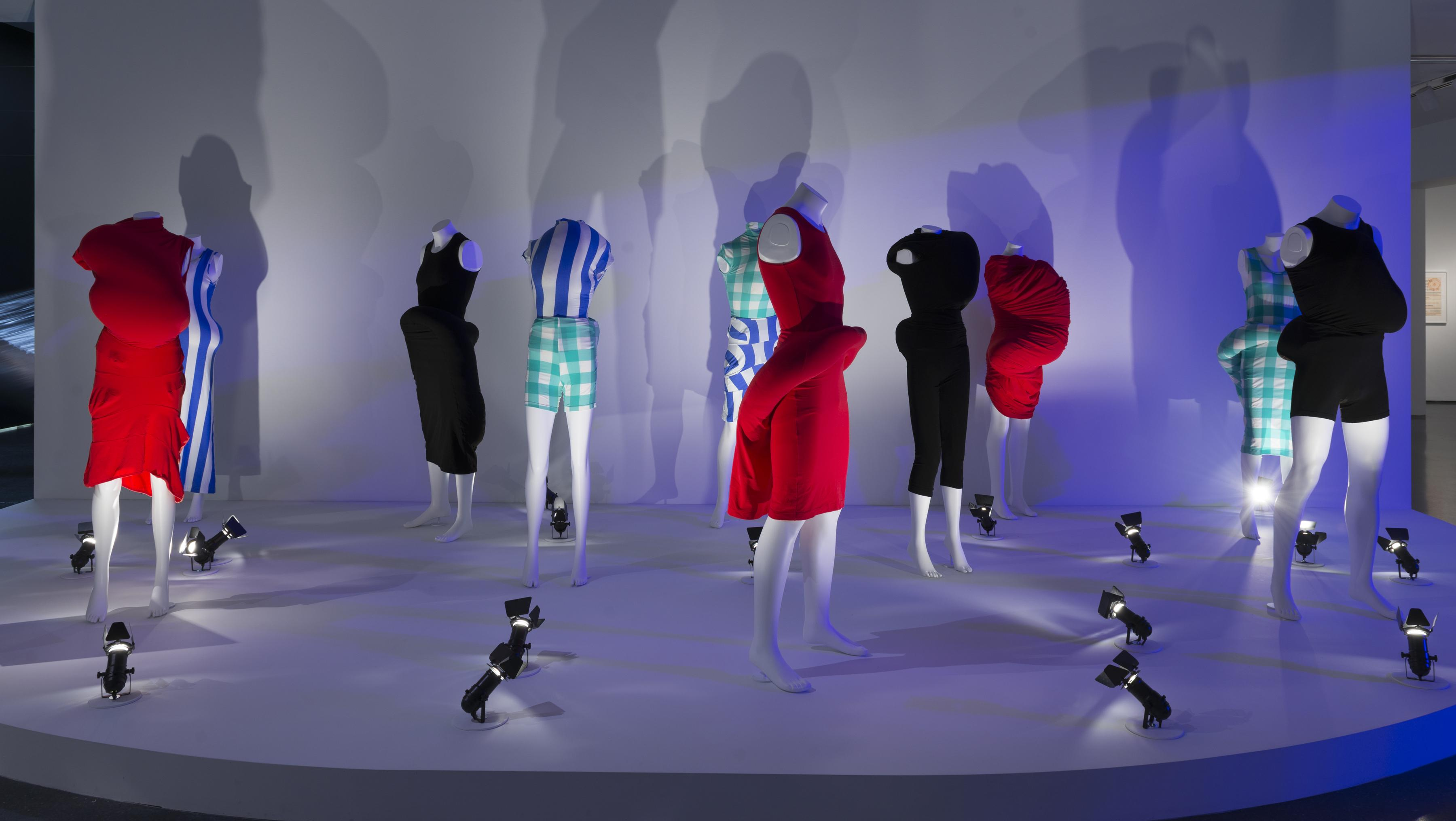 Ten headless mannequins dressed in clothing with unusual bulges are posed on a white platform and dramatically lit by spotlights on the ground.