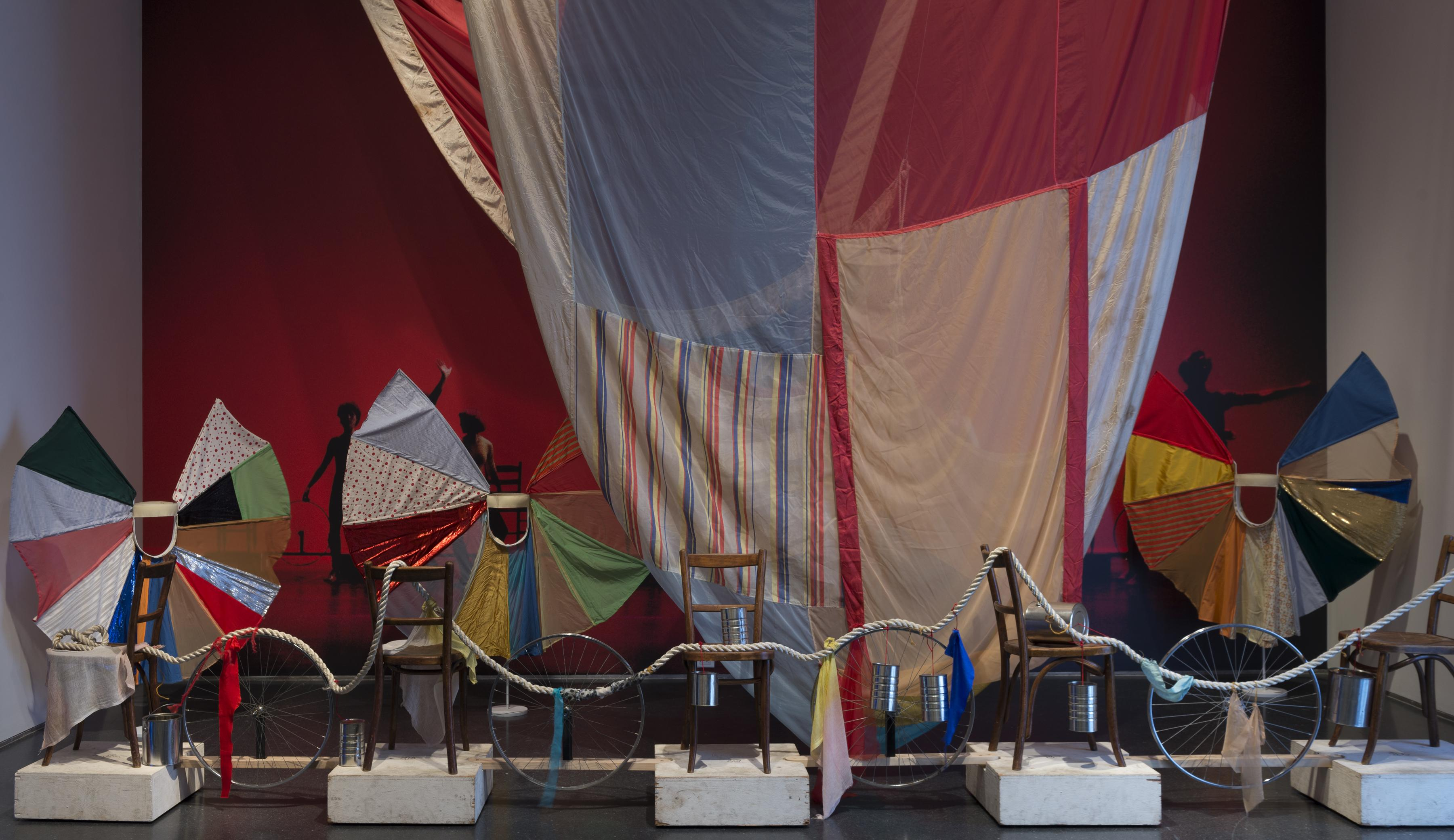 A thick white rope drapes across a row of chairs sitting on white blocks interspersed with silver bicycle tires. Behind them, a multicolor quilted fabric hangs from the ceiling in front of a red wall, and three smaller quilted fabrics fan out in imperfect circles.