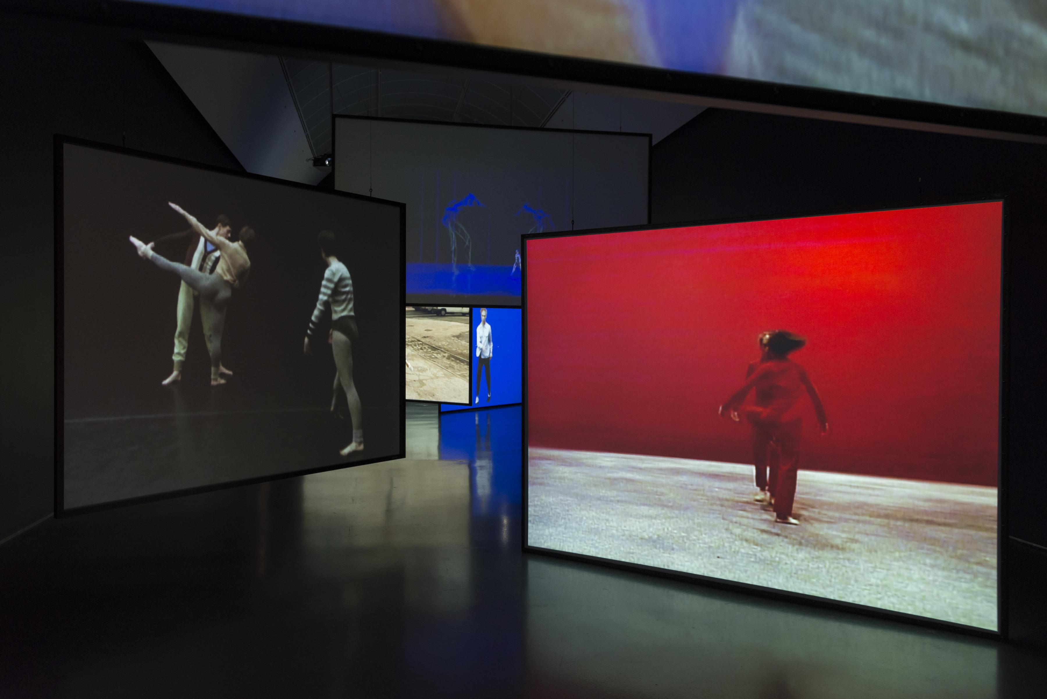Large projection screens hung at various heights and angles fill the dimly lit gallery. Videos projected on the screens show dancers in different performances and configurations.