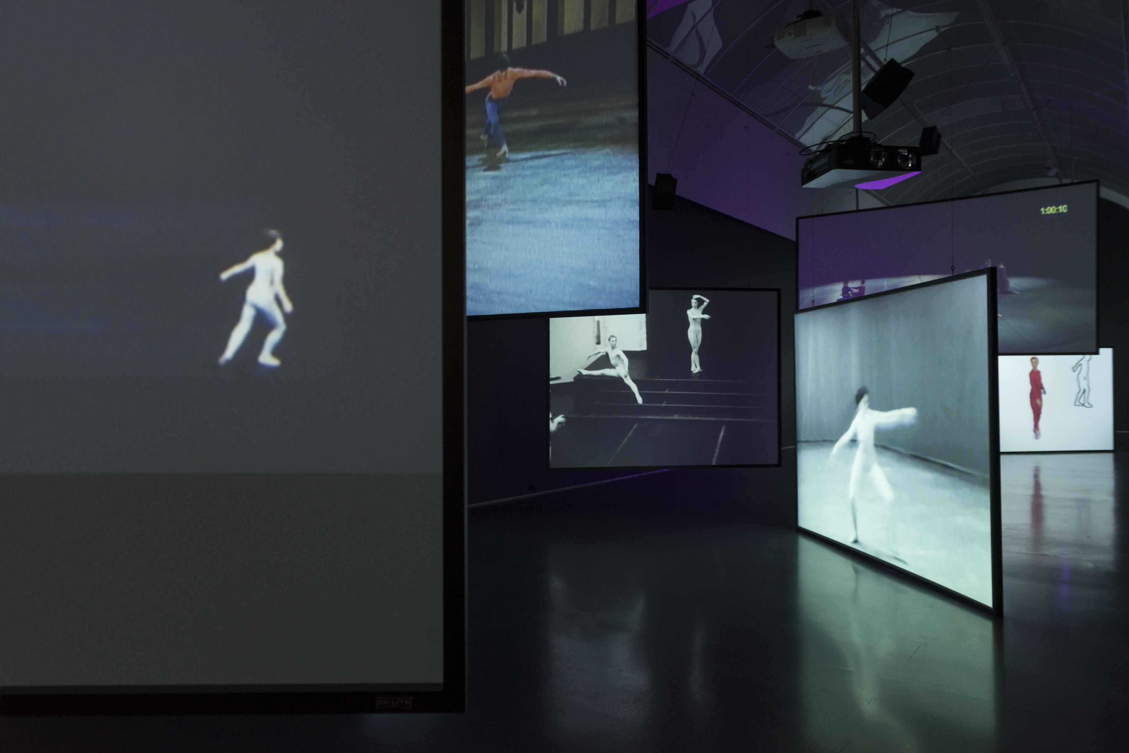 A large room is filled with projection screens hung at different heights and angles. The screens depicts dancers performing choreography.