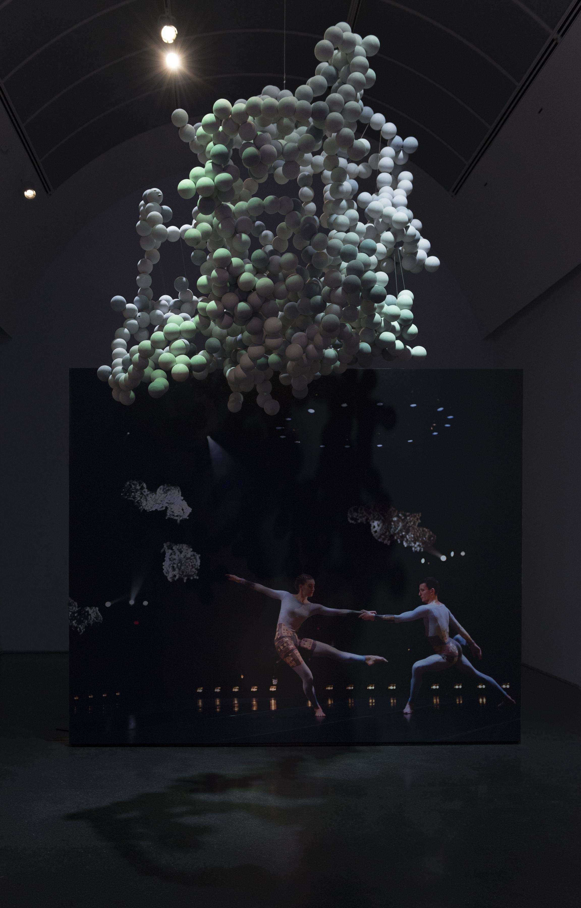 In a dark, dramatically lit space, a large amalgam of white balls hangs from the ceiling while a photo of two female dancers in unitards is visible on the wall.