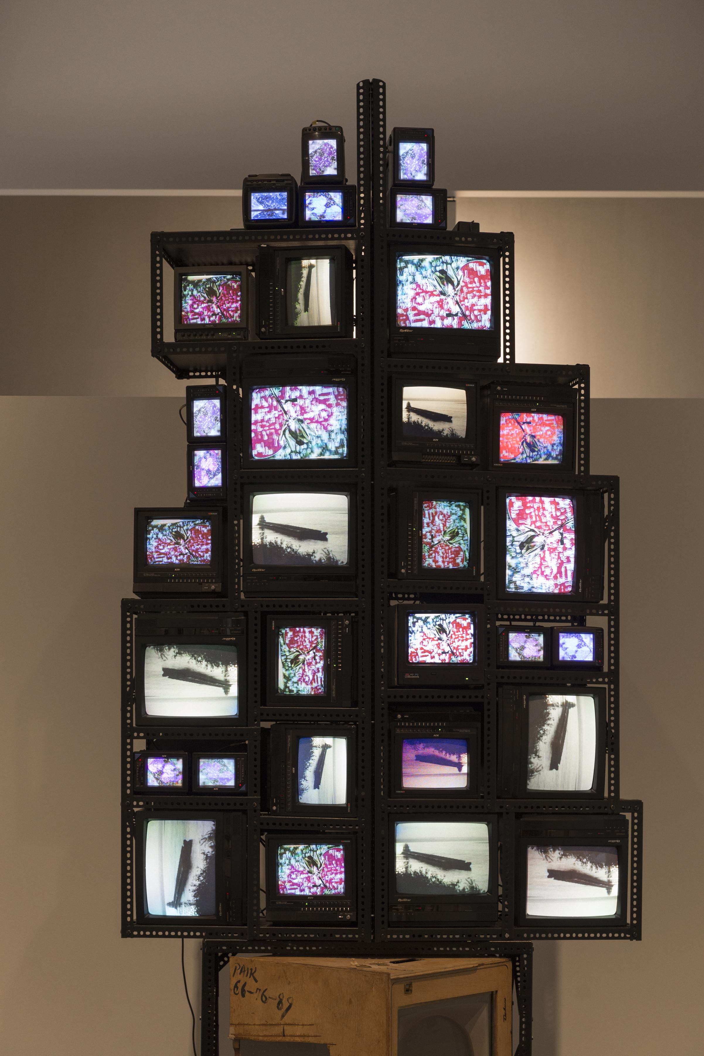 Cathode ray televisions of medium to small size are stacked on top one another at varying orientations and held together by perforated metal brackets. Two different images are repeated on the different televisions: a black-and-white video of a barge on a lake and a color drawing of a flower on a patterned background.
