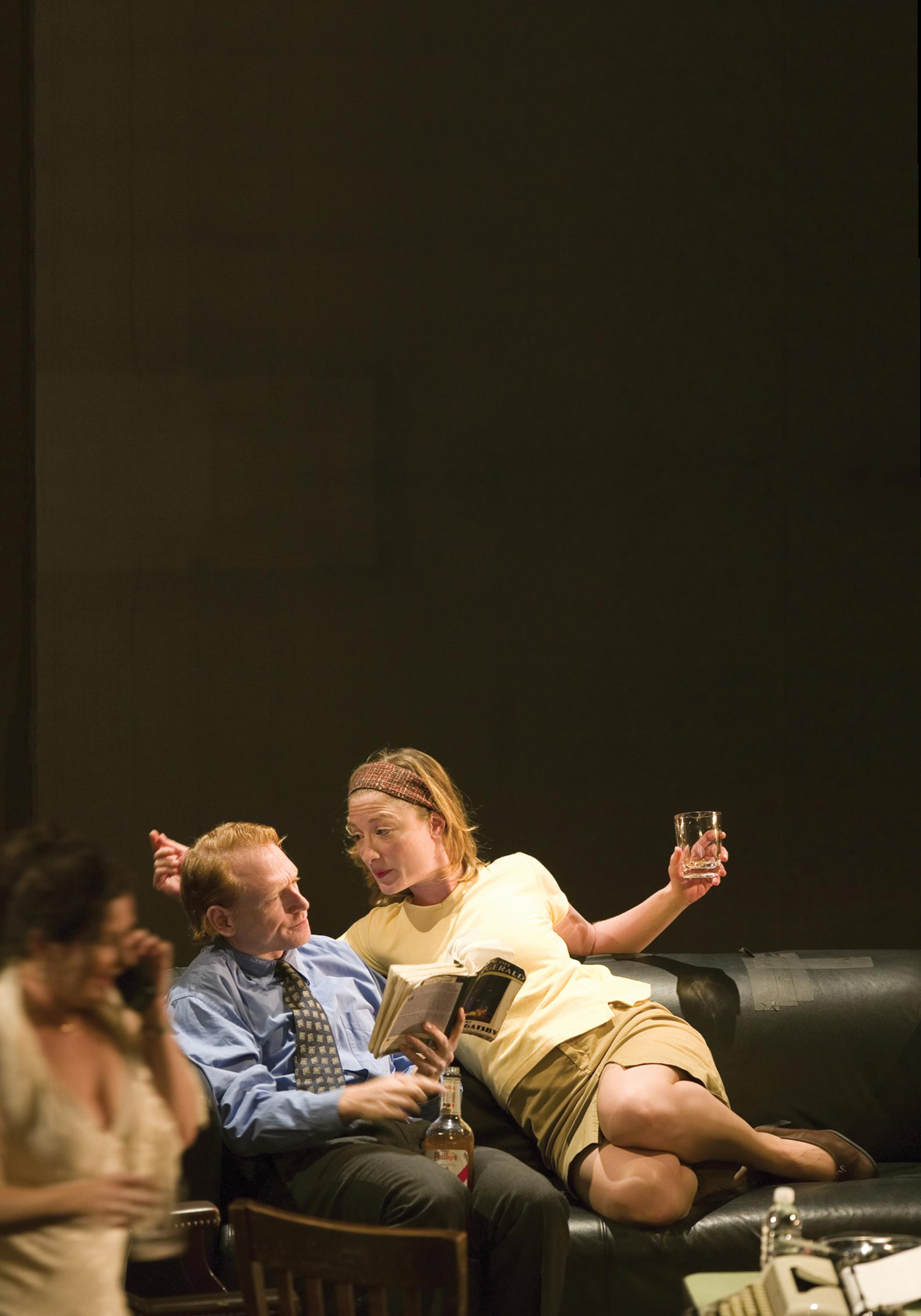 A woman and man lounge on a worn black leather couch, holding drinks and a bottle of liquor. The woman leans into the man while he reads a book. A blurred image of another woman is visible in the foreground, walking and talking on a mobile phone.