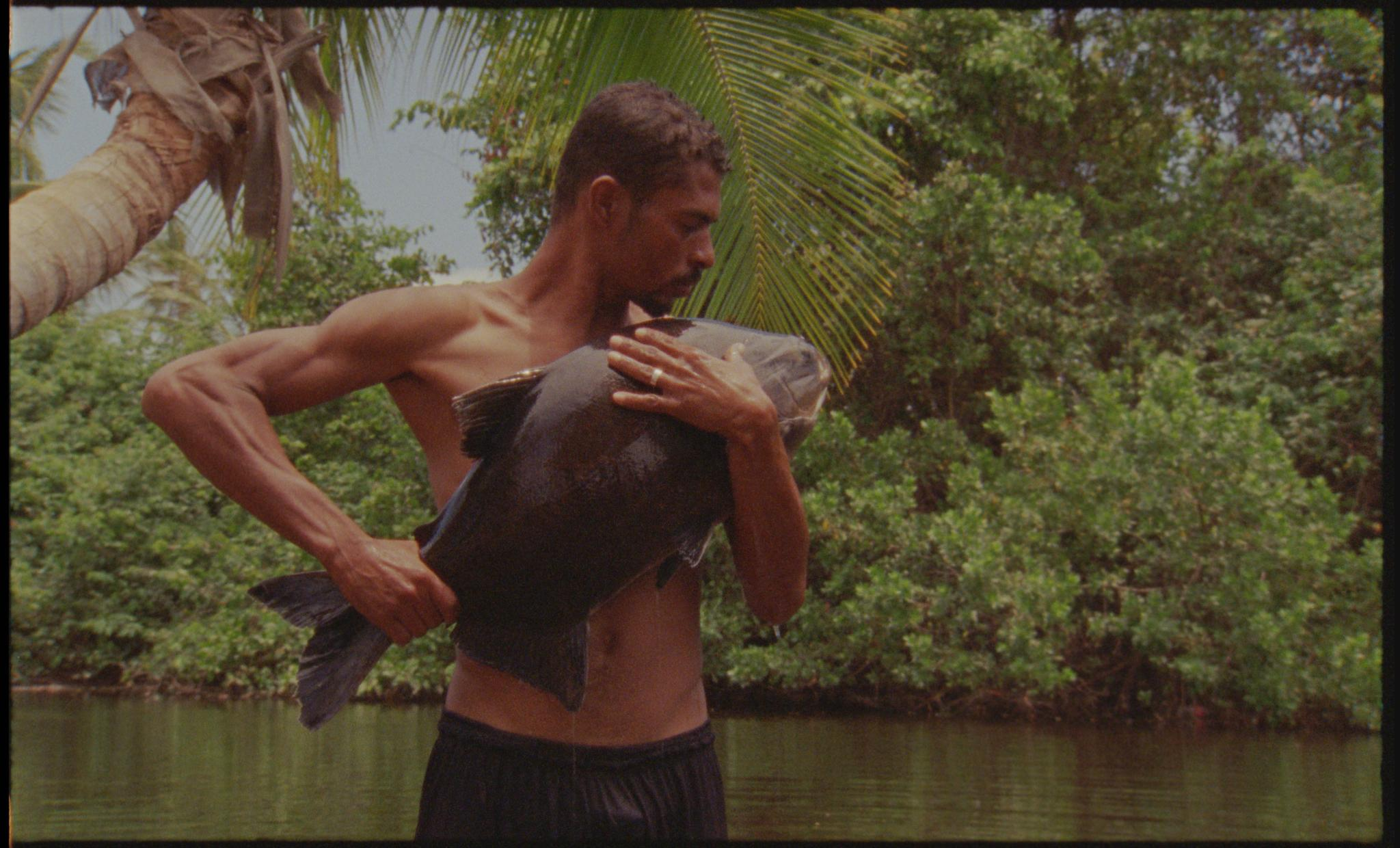 A man with tan skin and muscled arms holds a large fish to his bare chest. A palm tree and lush greenery line a body of water behind him.