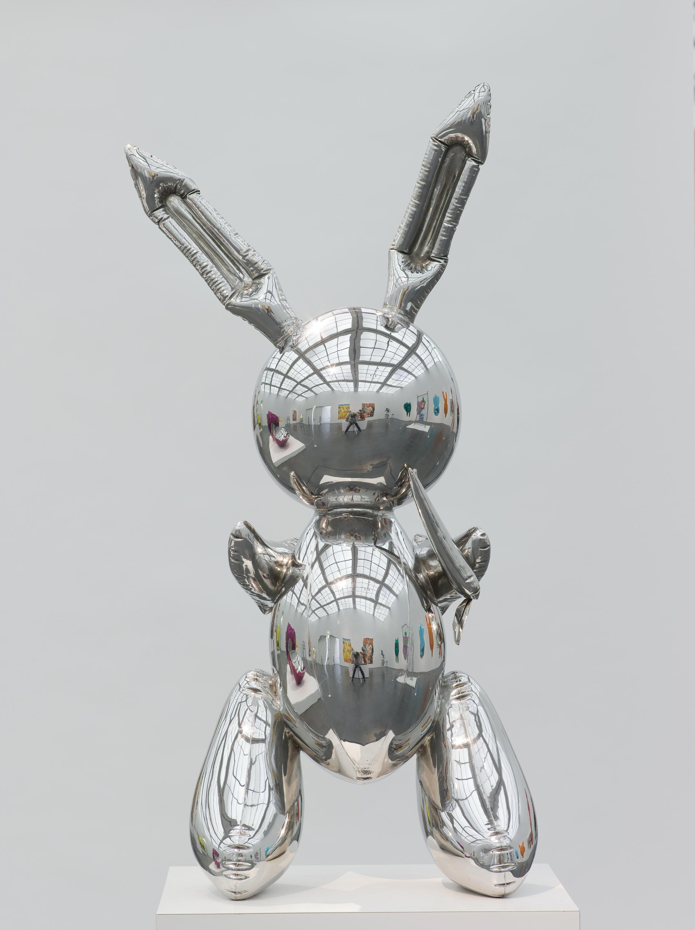 A sculpture that resembles a silver rabbit-shaped mylar balloon stands on a pedestal. A museum gallery is visible in the sculpture's reflective surface.