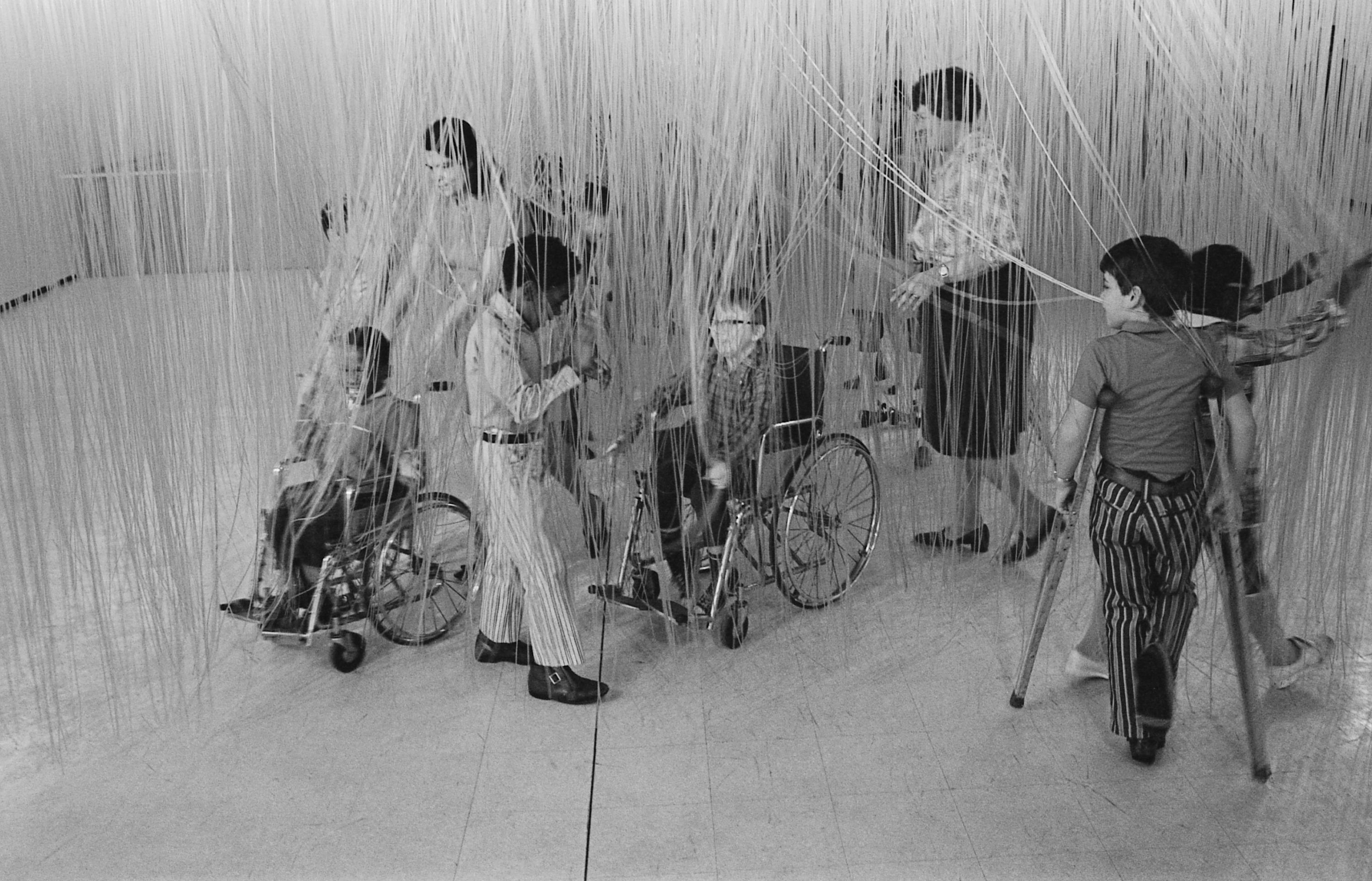 A group of children, some pushed in wheelchairs or using crutches, touches strands of an artwork hanging from the ceiling.