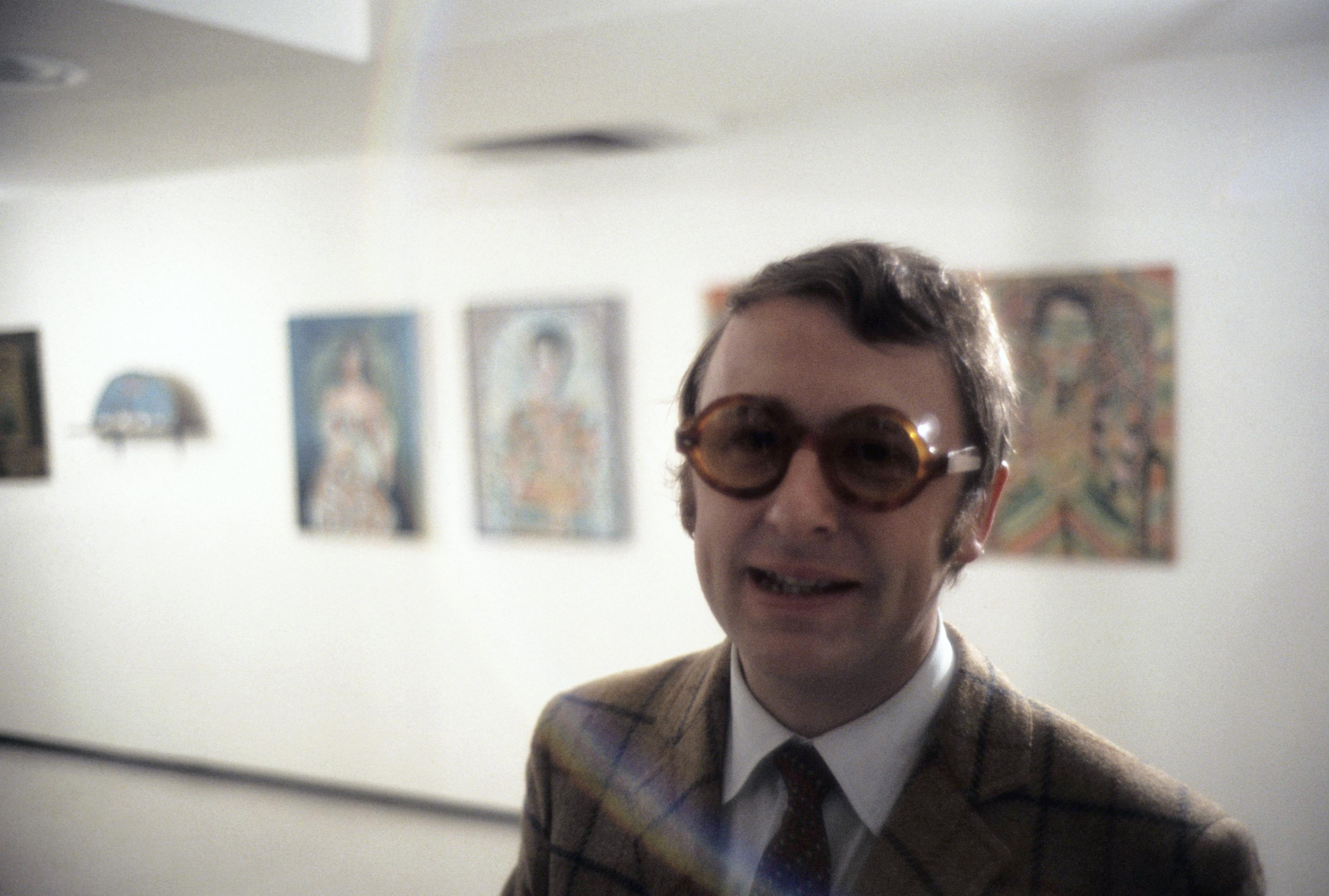 Jan van der Marck smiles, wearing dark tinted, round-framed glasses and a brown tweed sport jacket, with a white shirt and tie. Behind him are artworks hung on a white gallery wall.