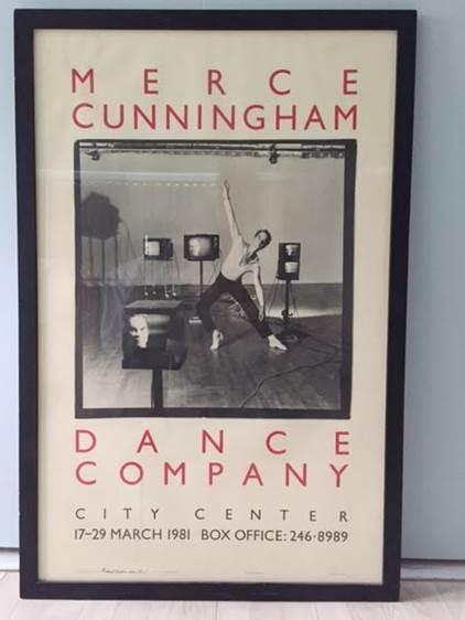 A framed poster of Merce Cunningham on the floor, leaning on the wall.
