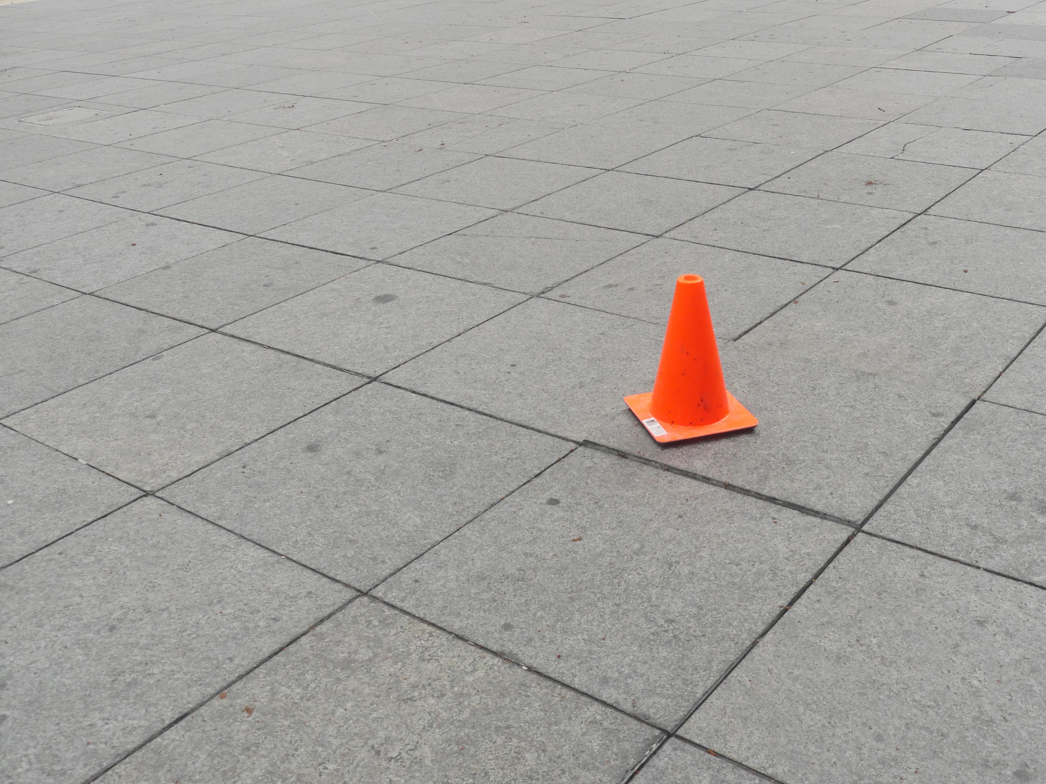 A lonely orange hazard cone sits on a grid of gray tiles.