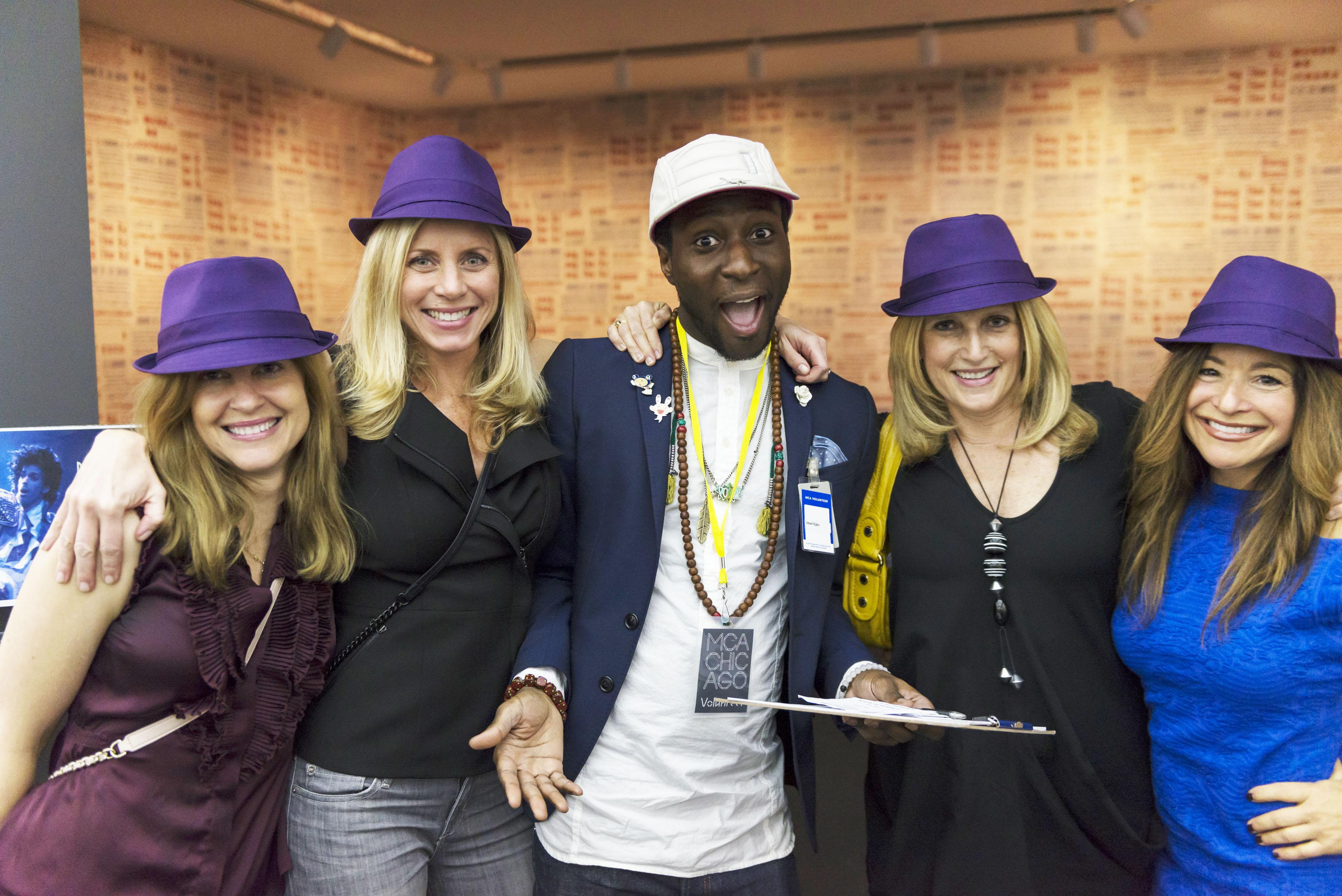 A group of five people pose, all but one wearing purple fedoras.