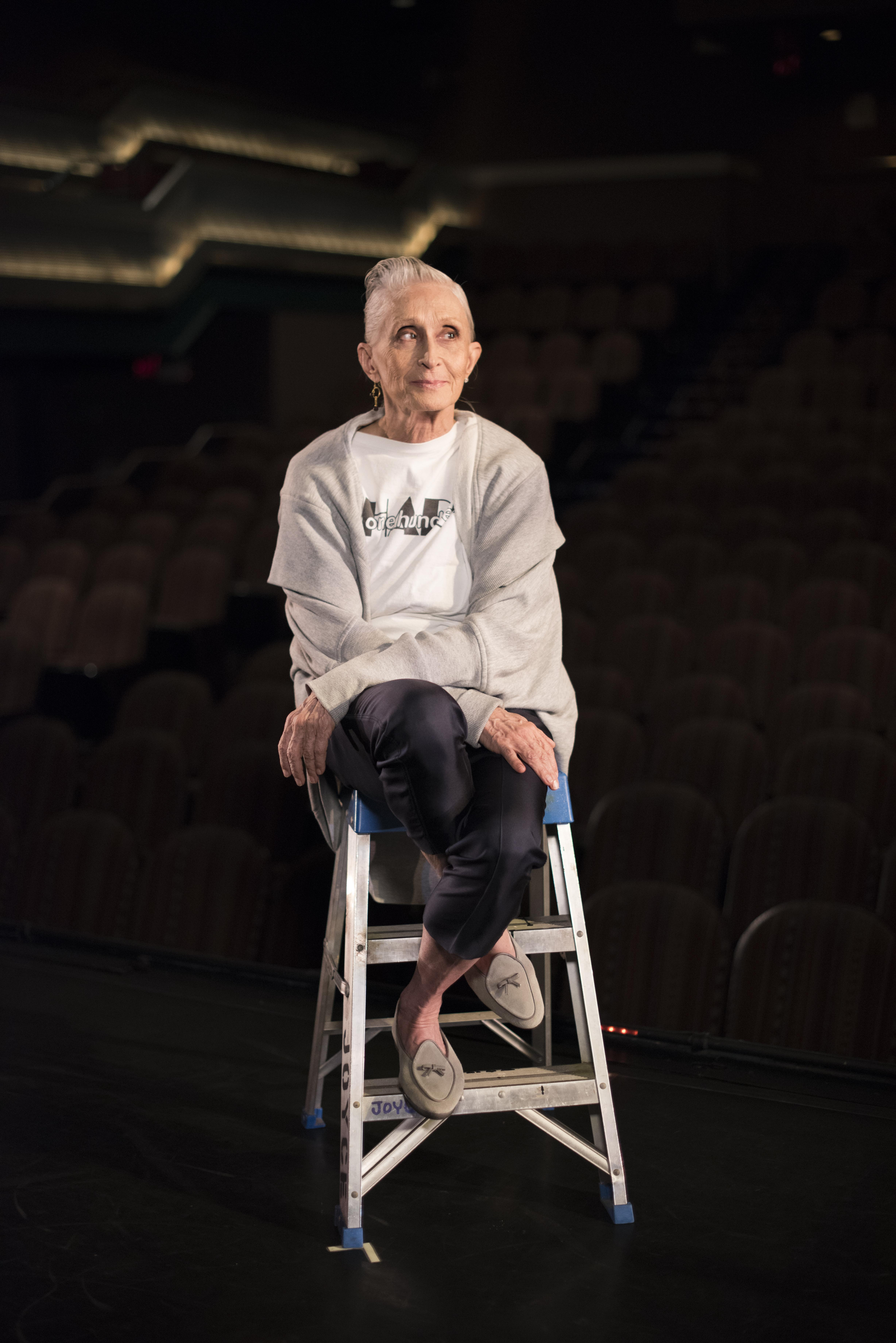 An older woman with her hair pulled back off her face, sits on top of a ladder on the edge of a stage with her legs crossed, as she looks to her left.