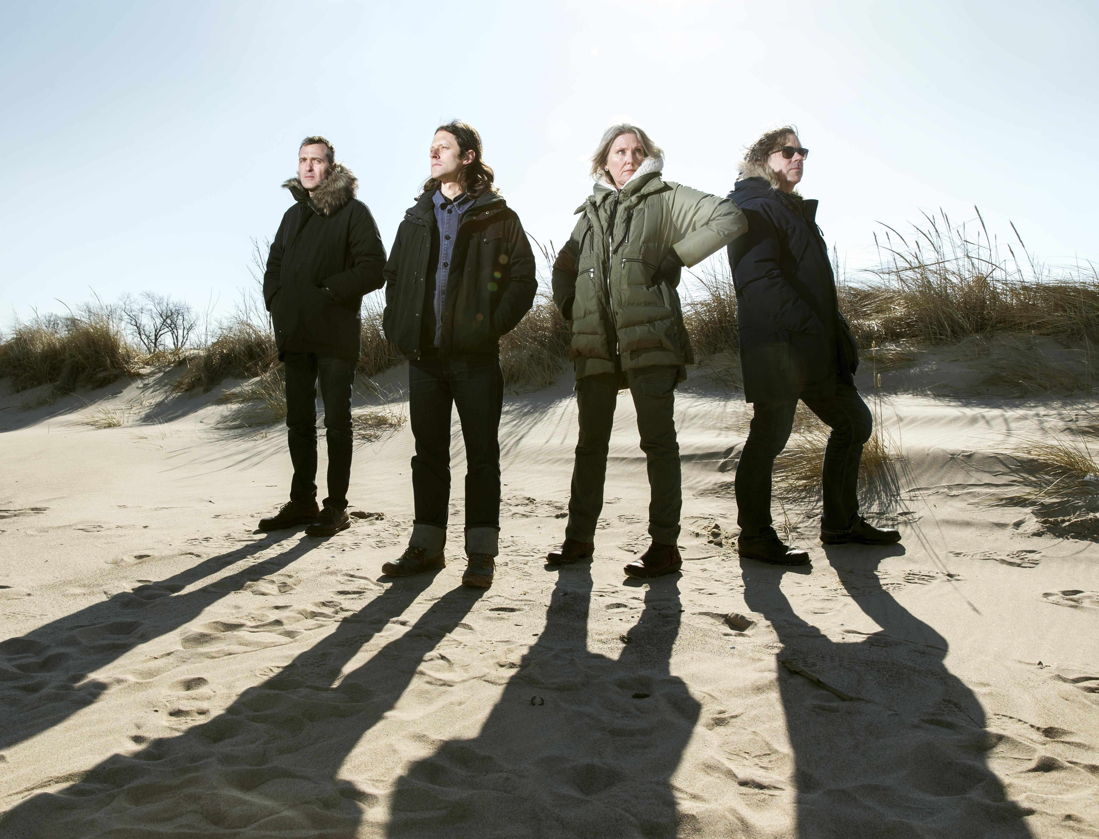 Three men and one woman stand on a beach on a sunny day wearing heavy parkas.