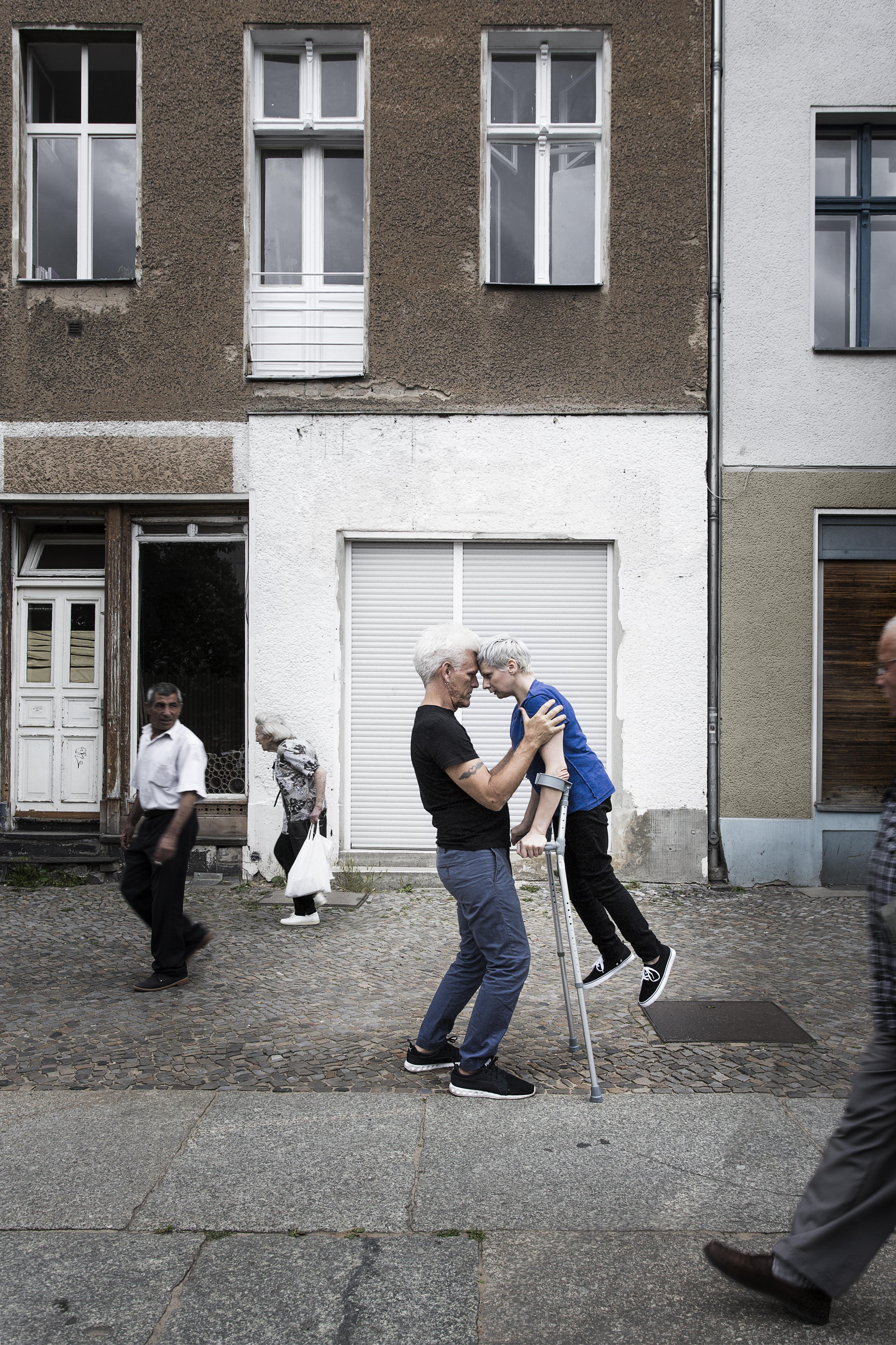 A man and woman lean on one another, their foreheads touching. The woman is held aloft by two long crutches she holds and her shoulders are steadied by the man.