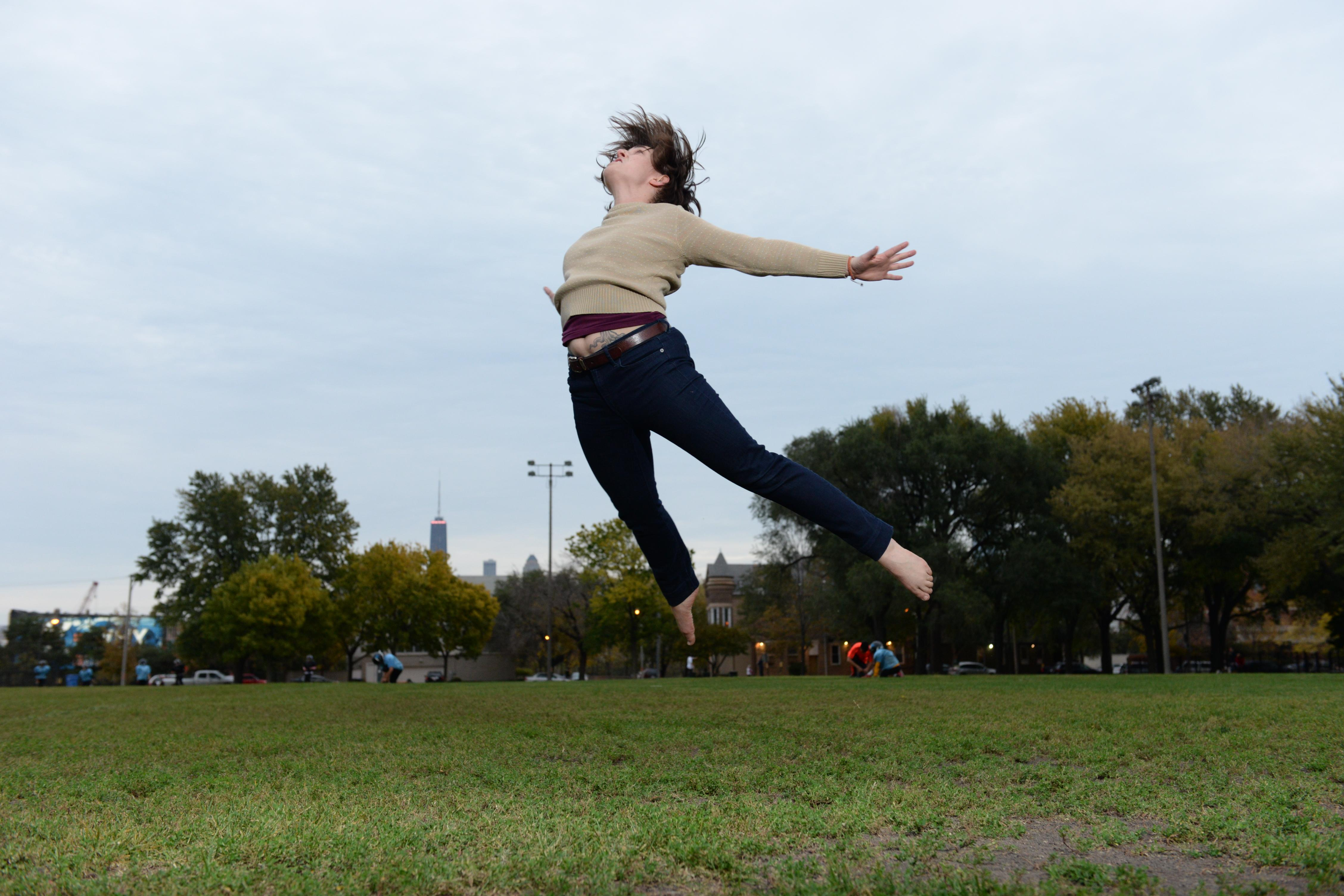 A person jumps leaning forward in mid air, with arms and legs stretched backwards.