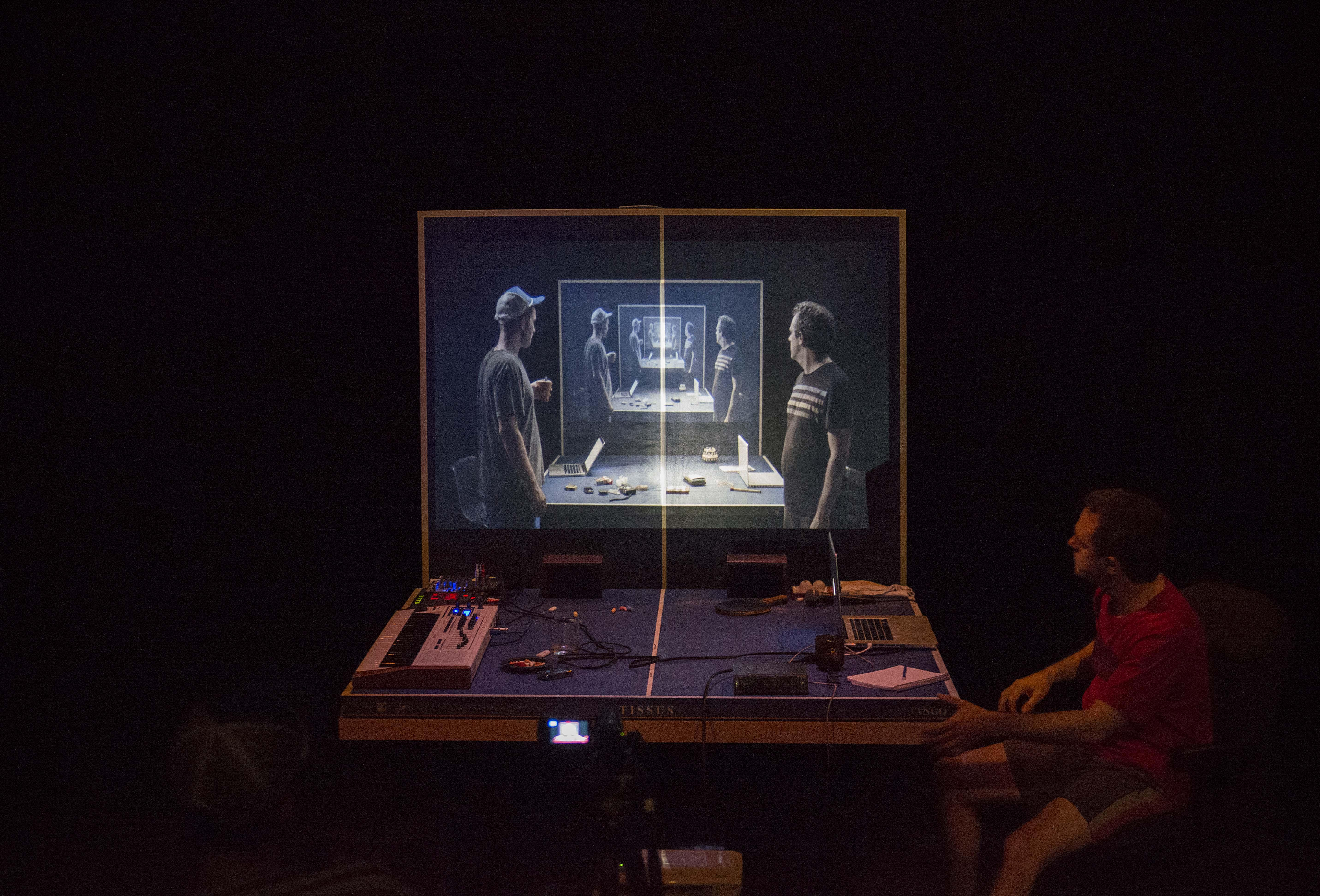 A man sits at a cluttered ping-pong table, looking at an image projected on the vertical rear half of the table. In the projected image, we see two men standing at the same table, their images repeating and receding into the distance.