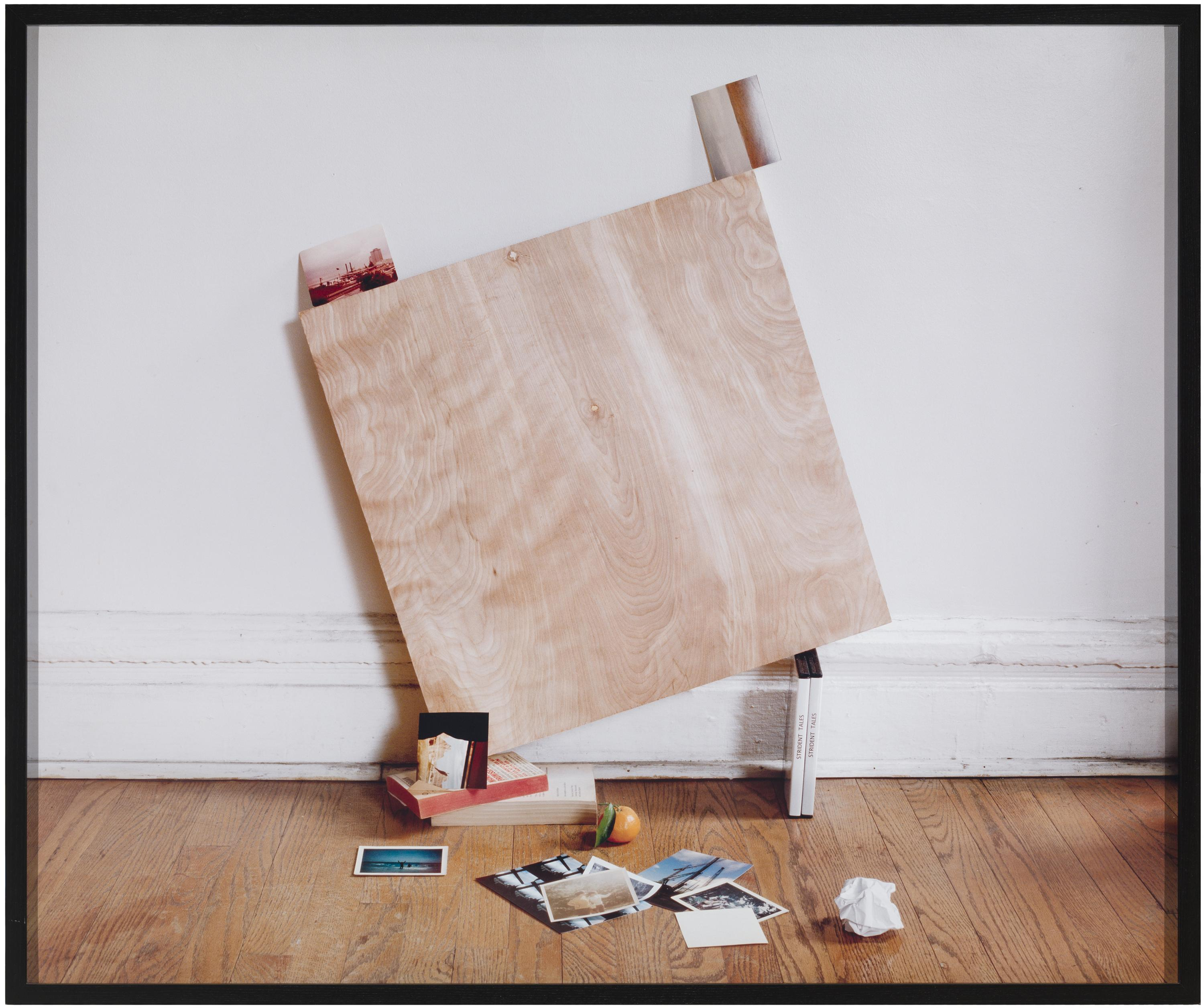 A square, wooden board precariously balanced on books leans against a white wall in a room with a hardwood floor scattered with photos.