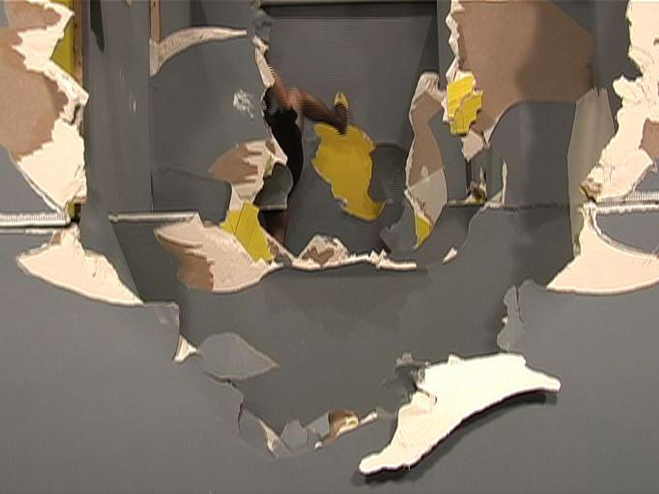 Layered gray walls are seen head on, receding into the middle distance. Each wall has a rough hole through it, forming a tunnel through which successive walls are visible. The broken edges of each hole are cream, brown, and mustard. At the end of the tunnel, a person's blurry leg wearing a yellow shoe kicks upward.