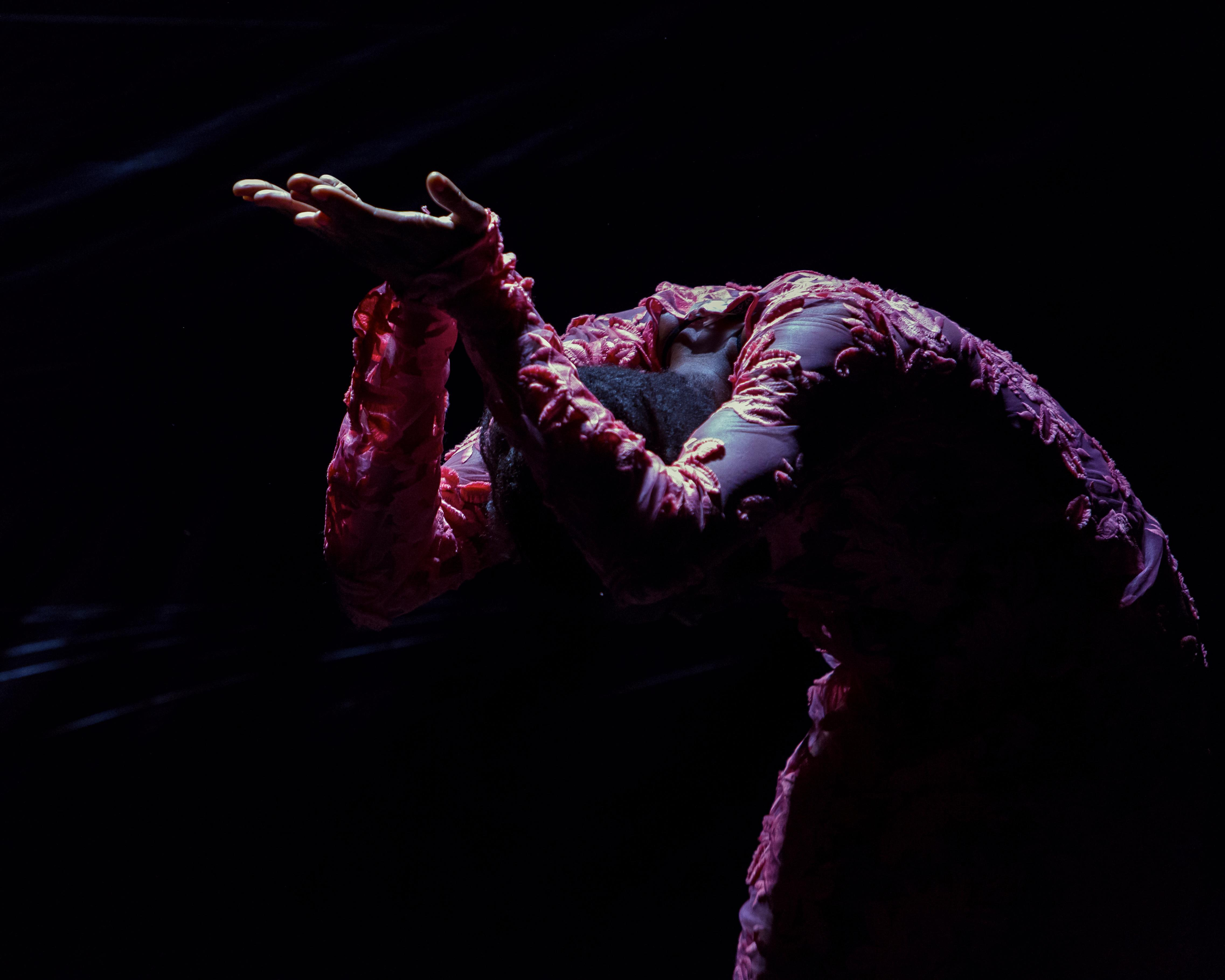 A lit figure against a dark background wears an embroidered costume and bends forward from the waist, arms raised and palms turned upward, and head faced downward, hidden from view.