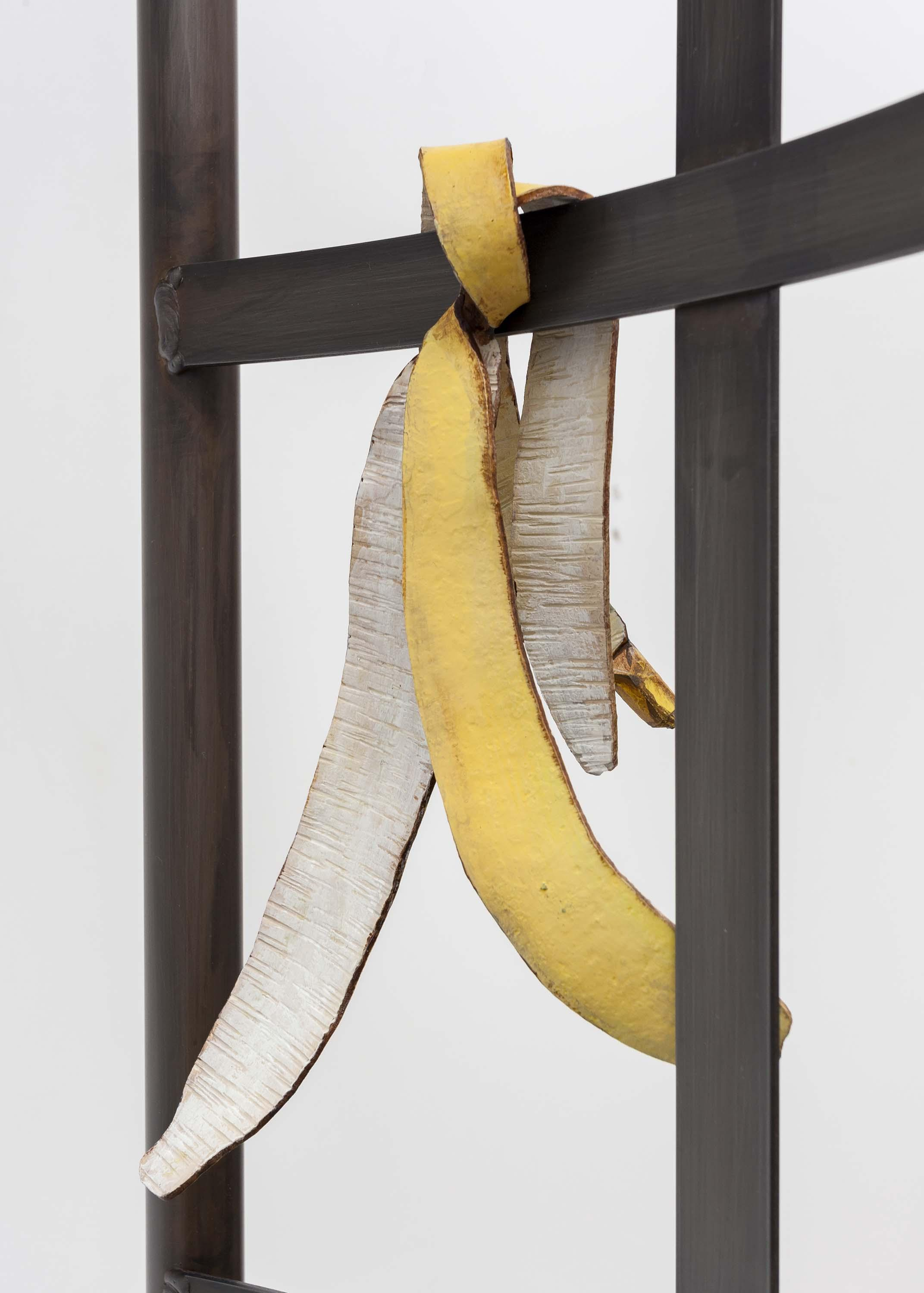 A close-up image shows a steel frame with a banana peel hanging off of it.